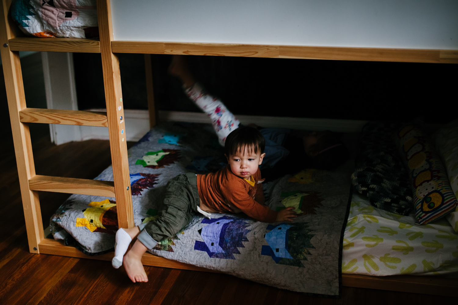 image of boy halfway on bed with one sock on and one sock off from family documentary photography session in atlanta