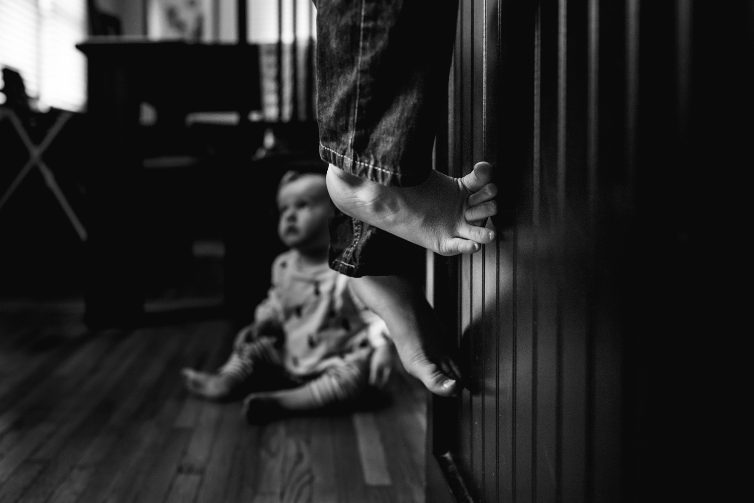 image of feet climbing a counter with a baby in the background from family documentary photography session in atlanta