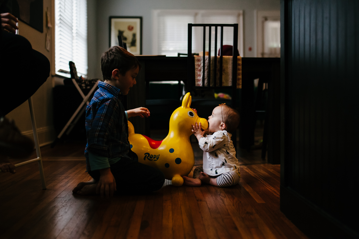 Baby puts her mouth on riding toy with brother watching from family documentary photography session in atlanta