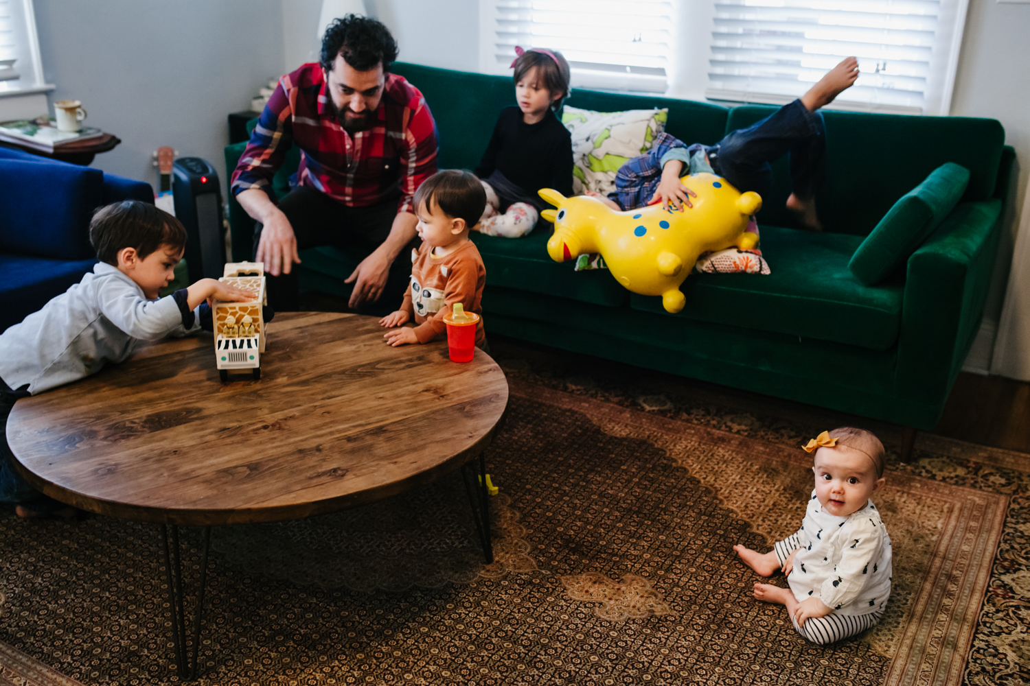 family playing in the living room with baby on the floor looking at the camera from family documentary photography session in atlanta