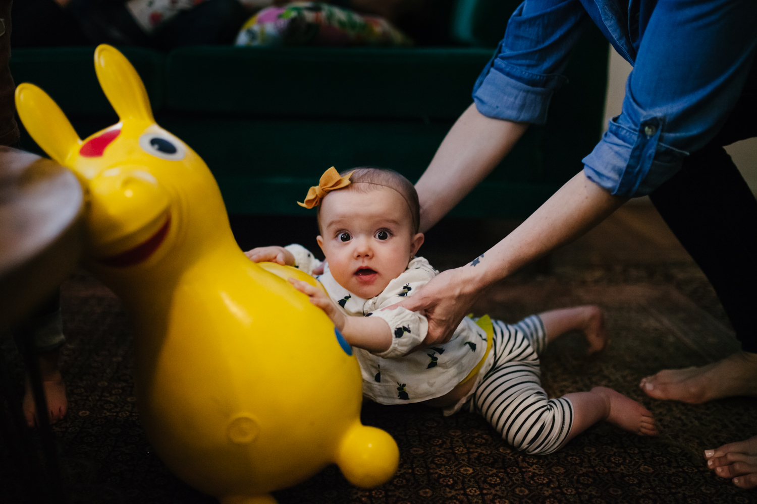 baby slipping off riding toy and being helped by her mother from family documentary photography session atlanta