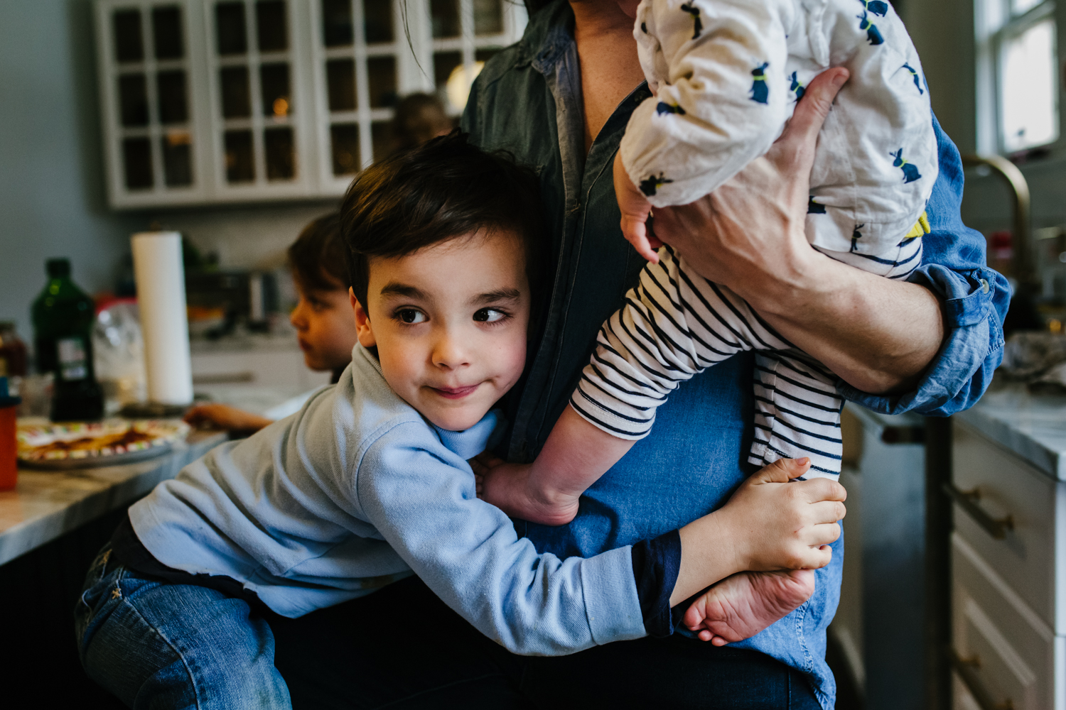 Boy hugging mom and holding onto baby's foot while mom holds baby from family documentary photography session in atlanta