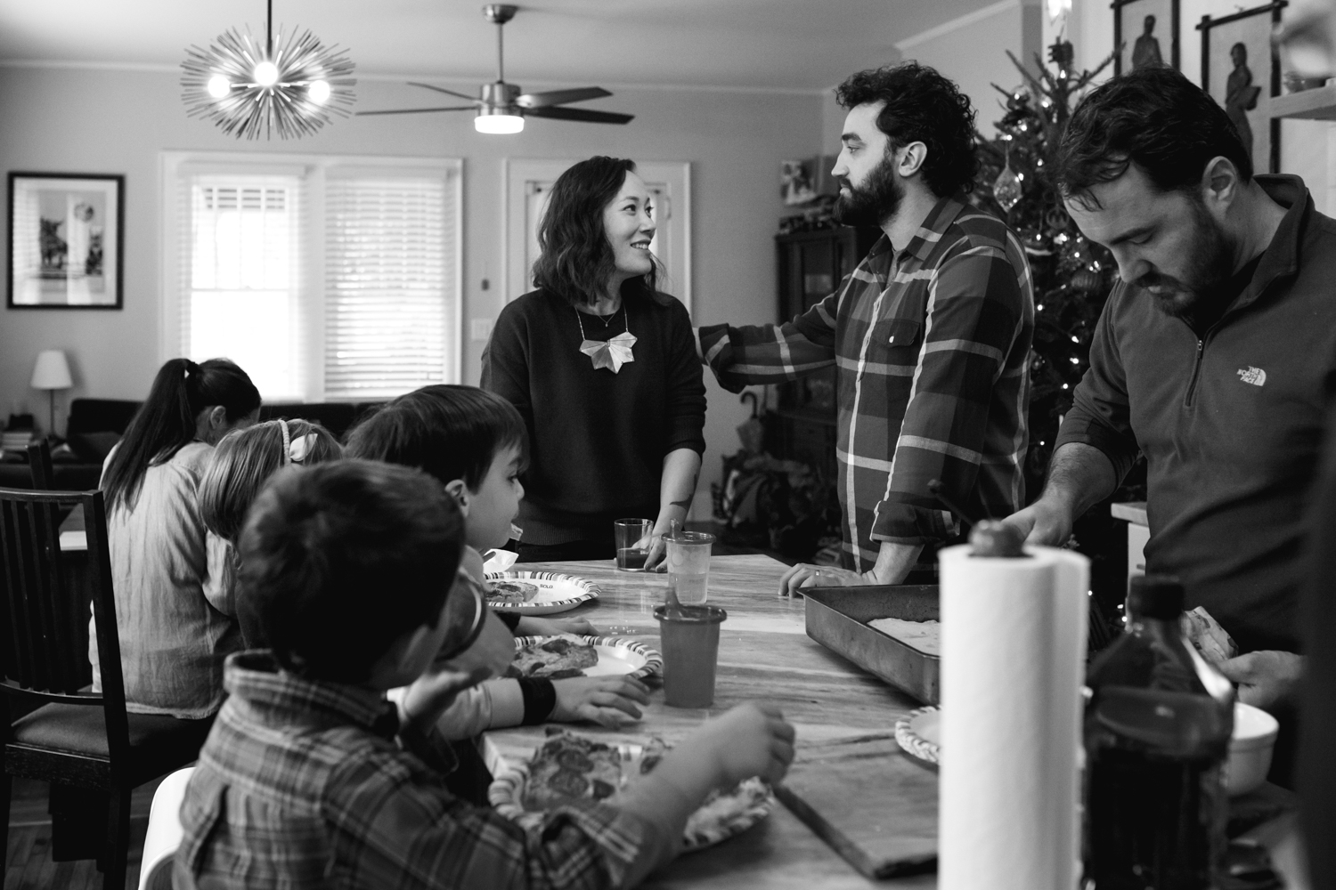 Husband and wife look at each other while a lot of different activity happens in the kitchen from a family documentary photography session in atlanta