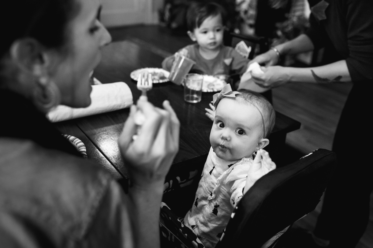 baby stops and looks at the camera while mom feeds the baby from family documentary photography session in atlanta