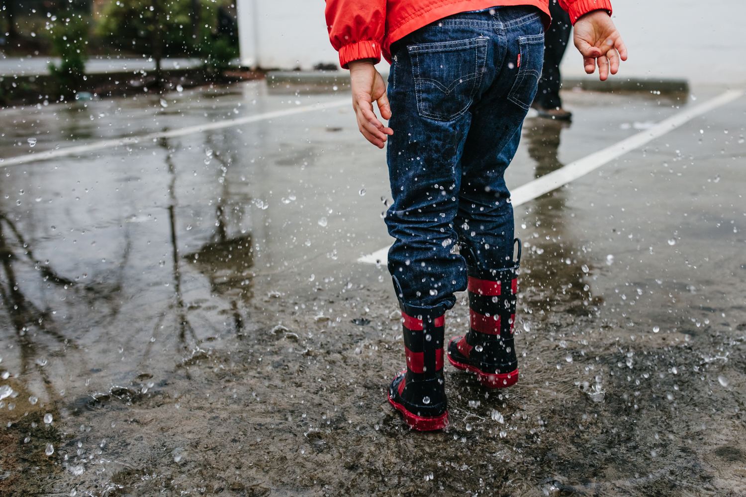 boy jumps in puddles in the rain from family documentary photography session in atlanta