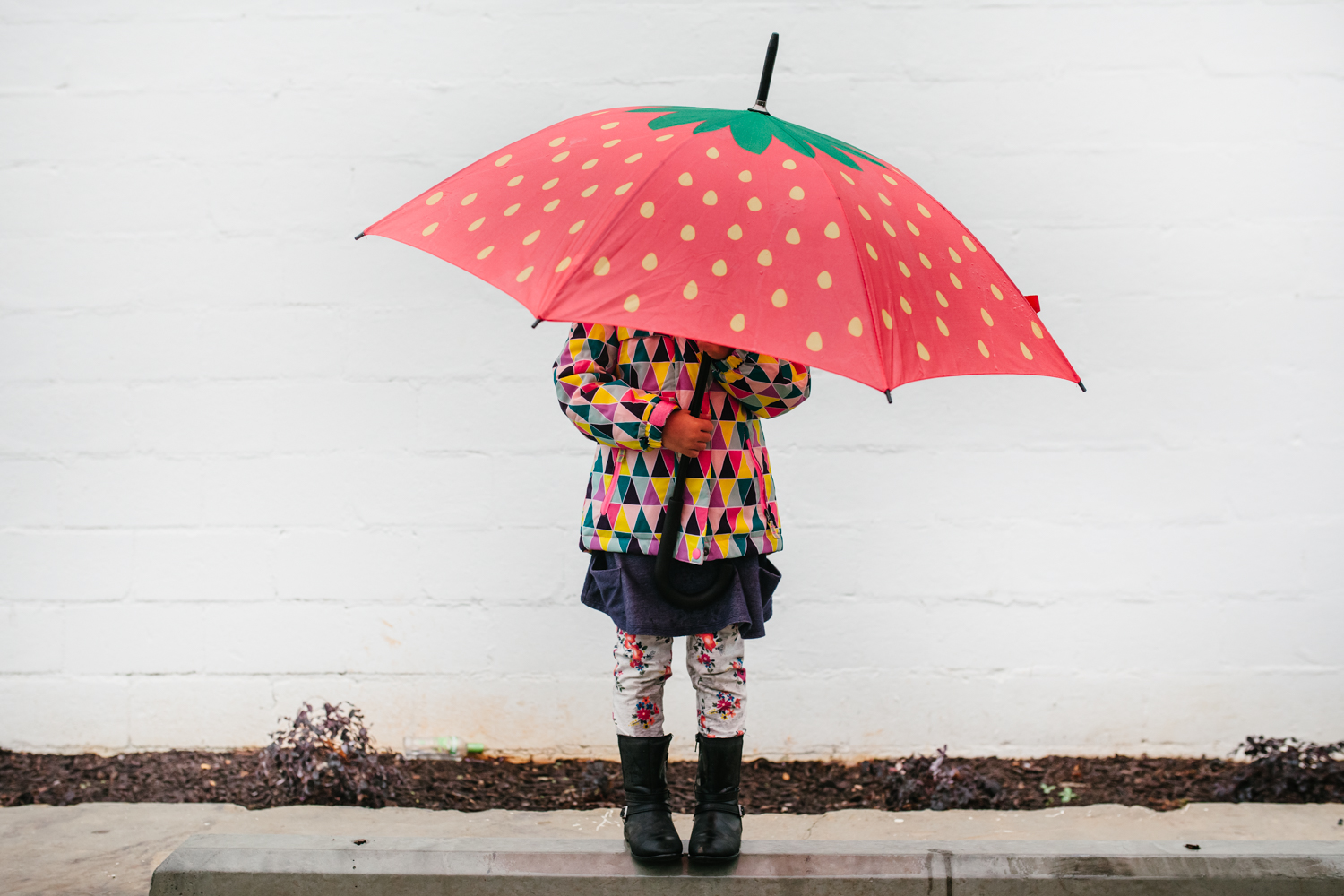 Girl holding umbrella hiding underneath it from family documentary photography session in atlanta