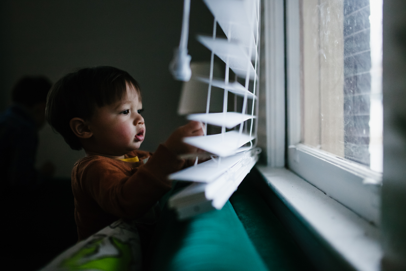 boy plays with blinds during family documentary photography session in atlanta
