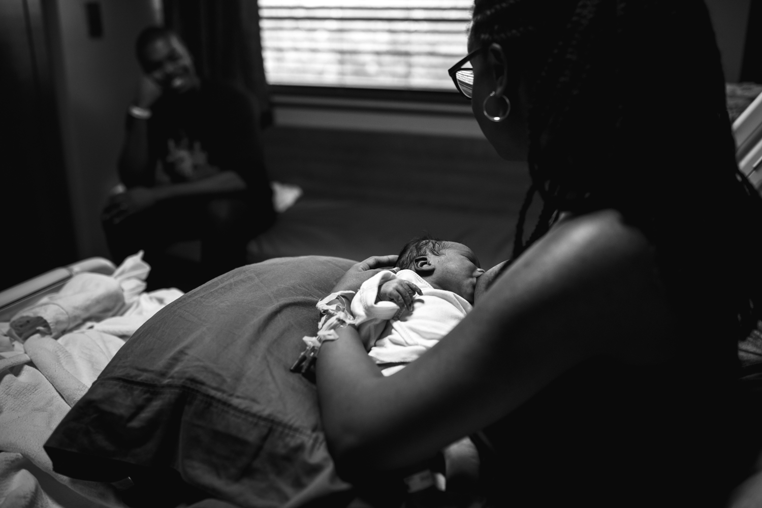 mother nursing newborn while father looks on from newborn documentary photography session in atlanta