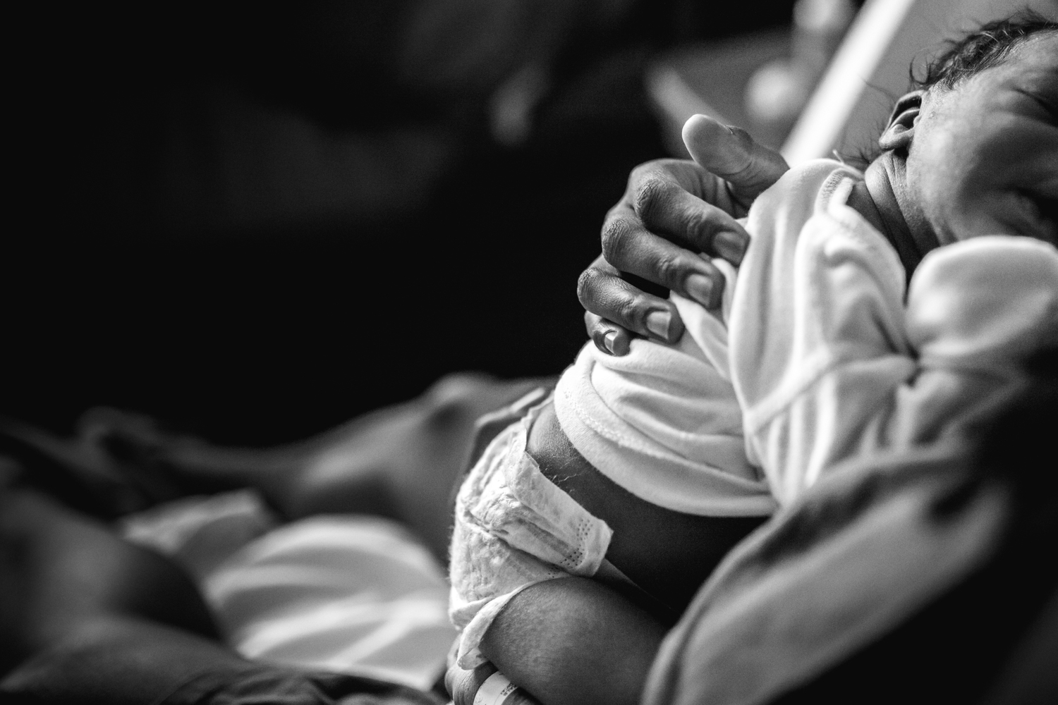 newborn nestles against mother's chest during newborn documentary photography session in atlanta