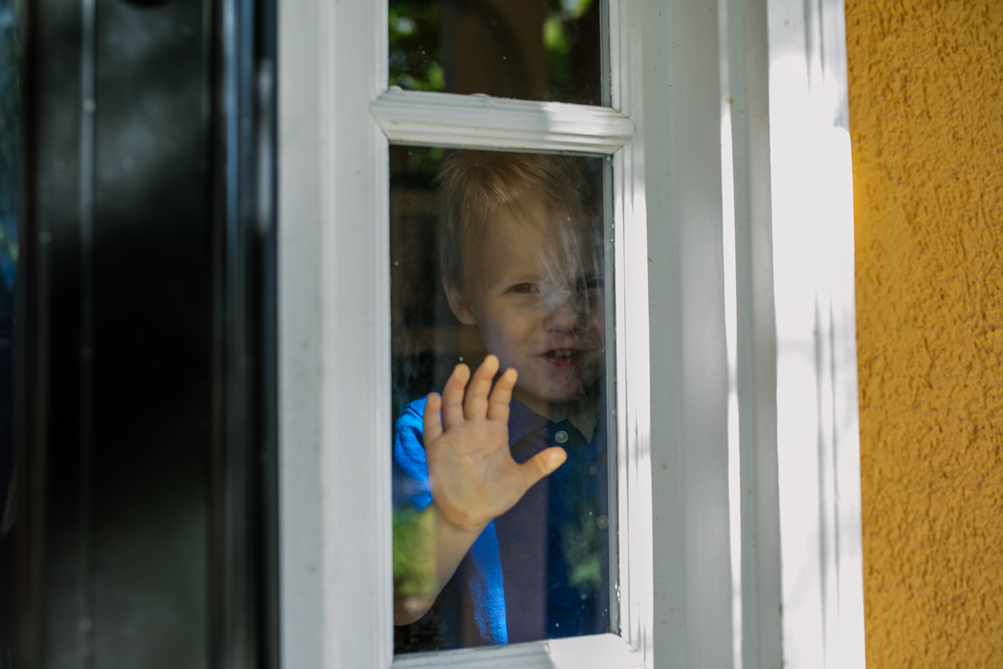 child with hand on window looking out of house
