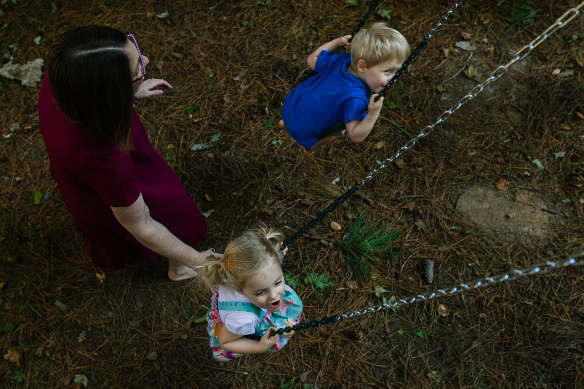 image from above of mom pushing two children on swings