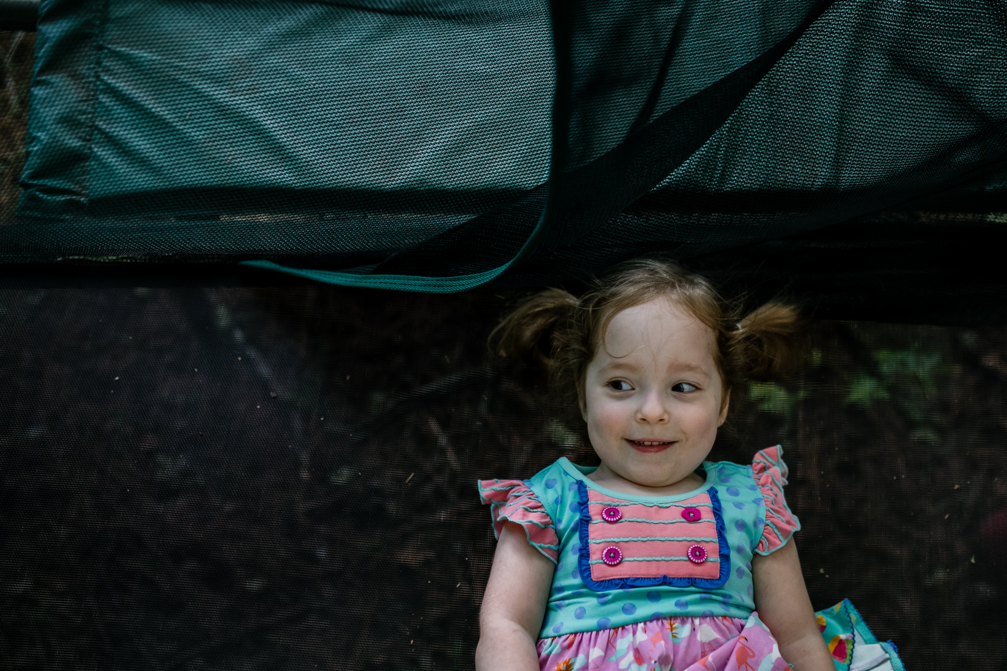 environmental portrait of girl lying on a trampoline