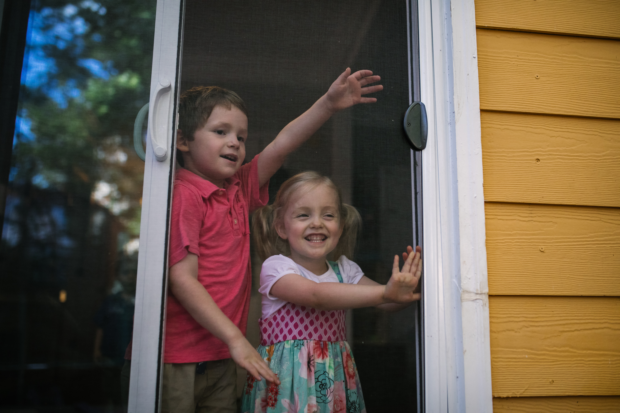 Boy and girl shutting screen sliding door