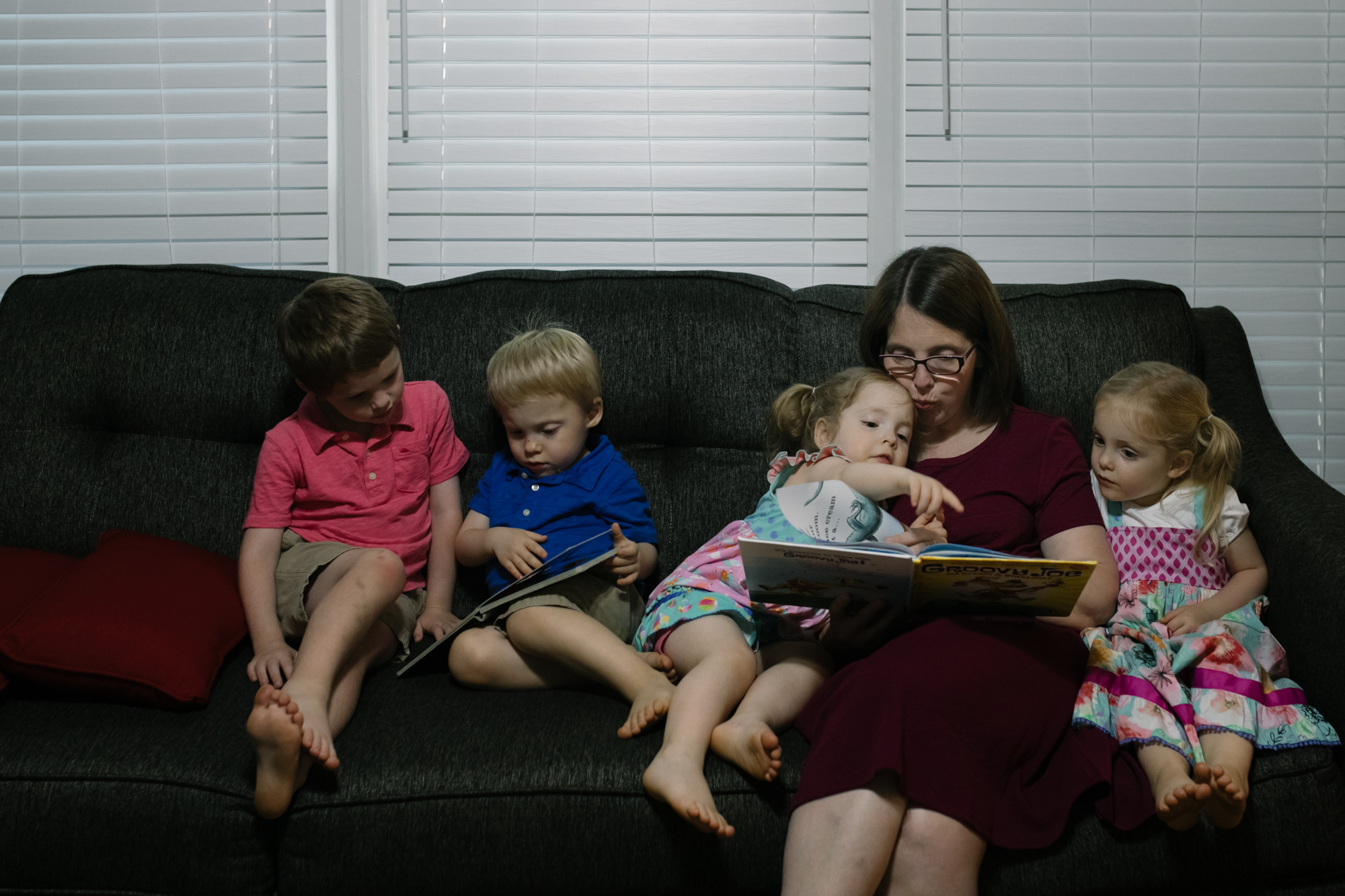 mother reading book to four children on the couch