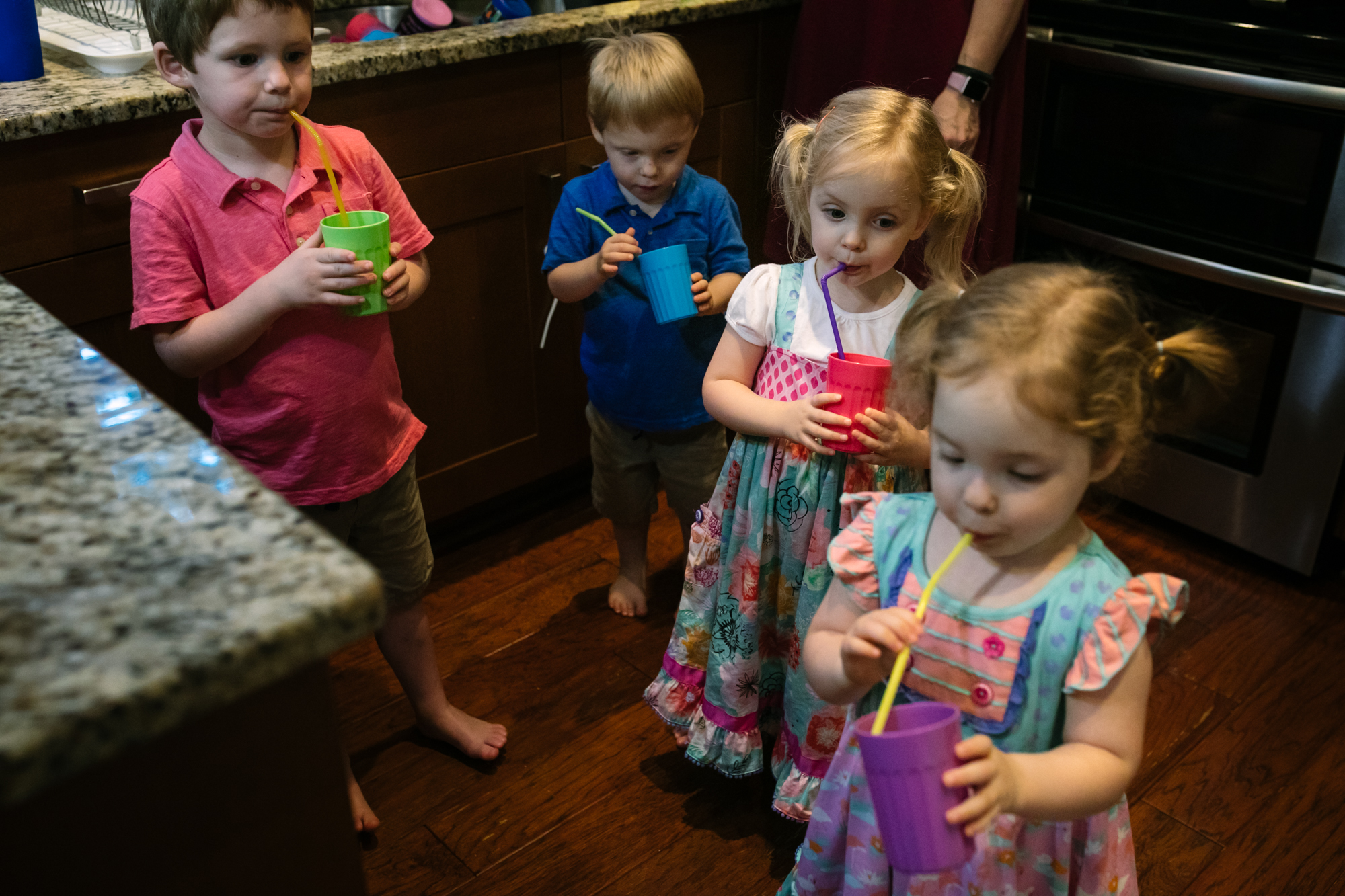 Kids drinking out of cups with straws in a kitchen