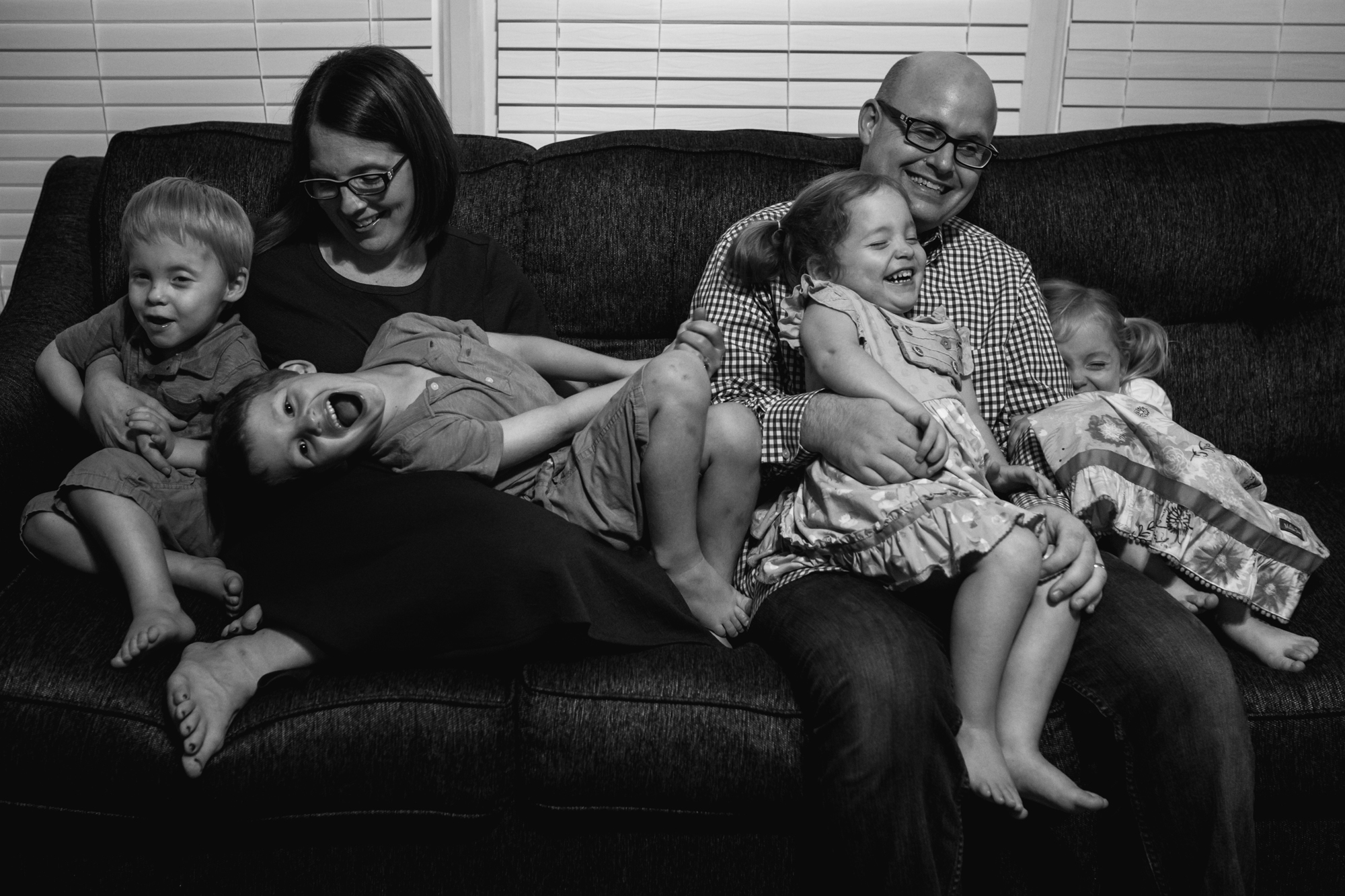 A family sitting on the couch with kids laughing and goofing