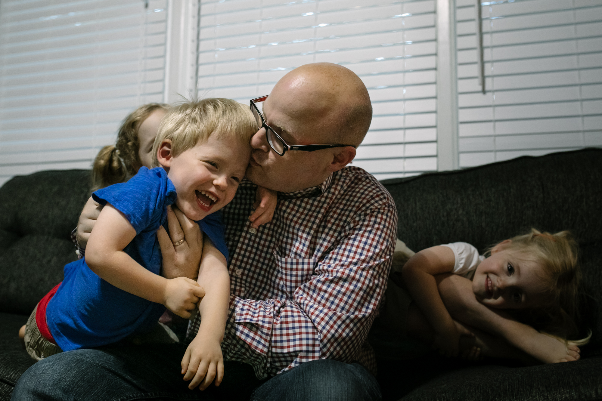 Dad kisses son who is smiling and girl in background holds onto another kid's legs