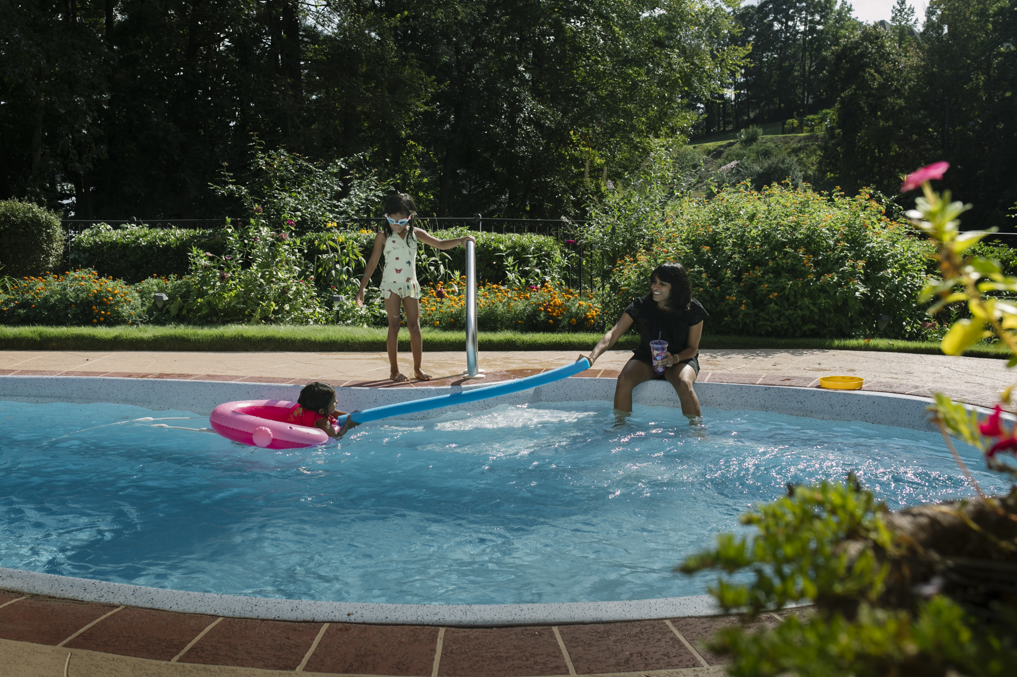 Mother holding a swimming noodle with her daughter in a pool while another daughter watches