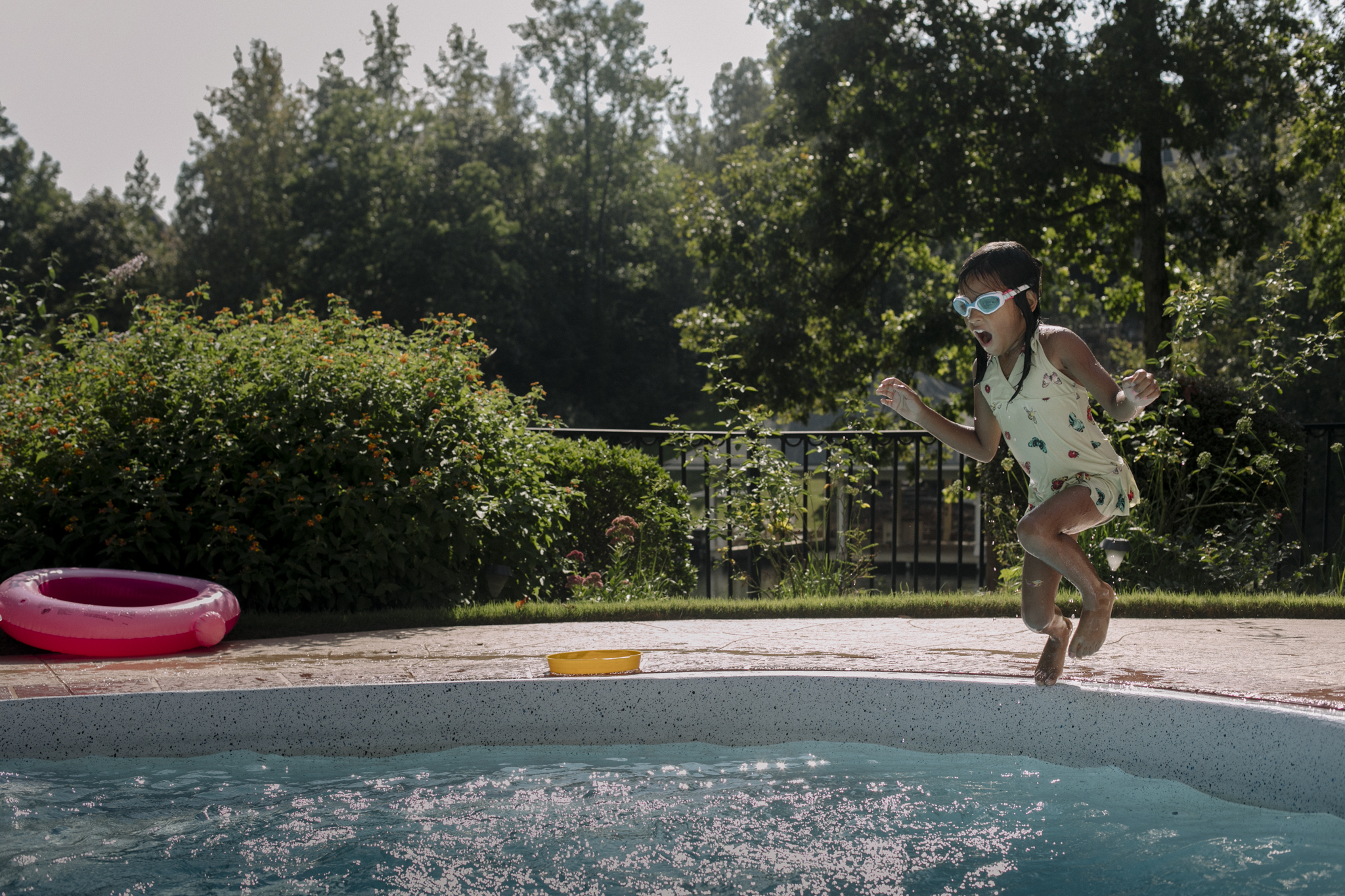 Girl with goggles jumping into the pool