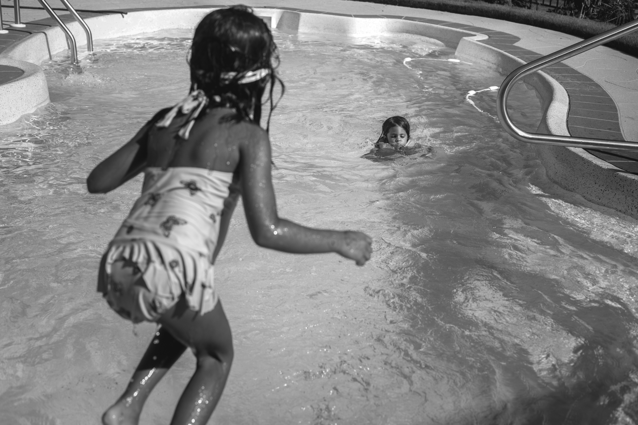 Picture from behind a young girl who is jumping into a pool where her sister is already swimming