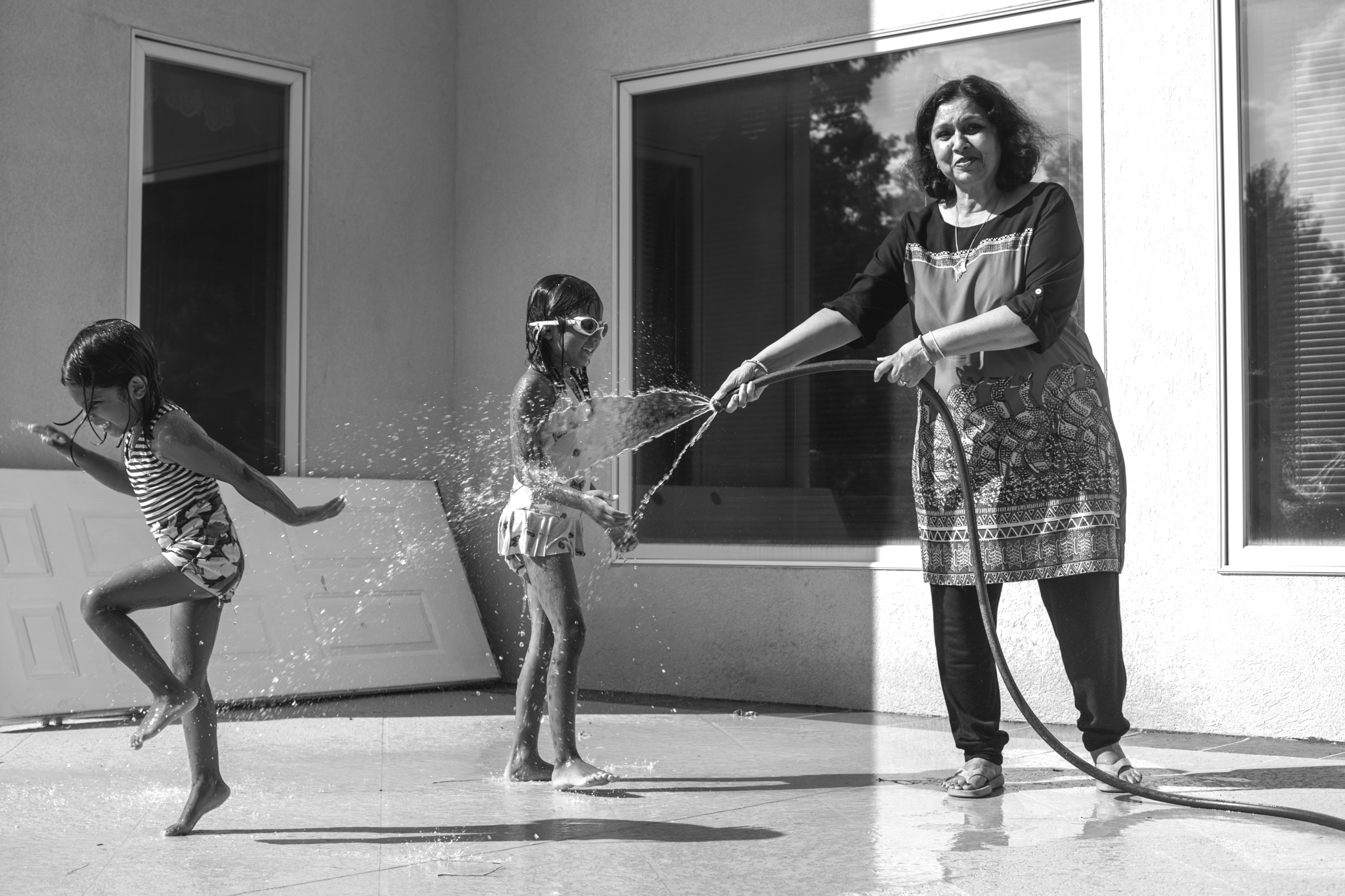 Grandmother spraying granddaughters with the hose