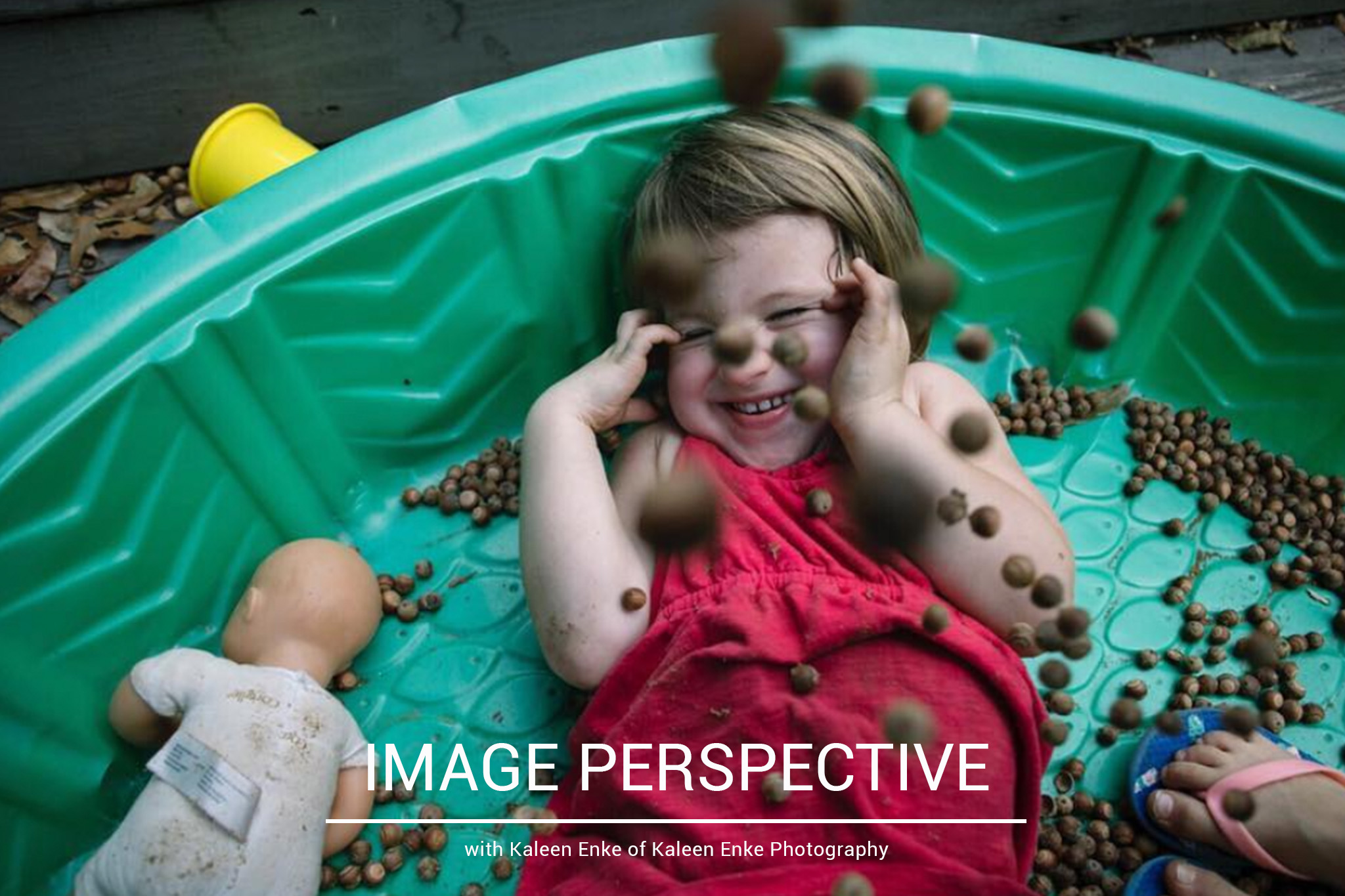 image from above of girl smiling while acorns are falling on her