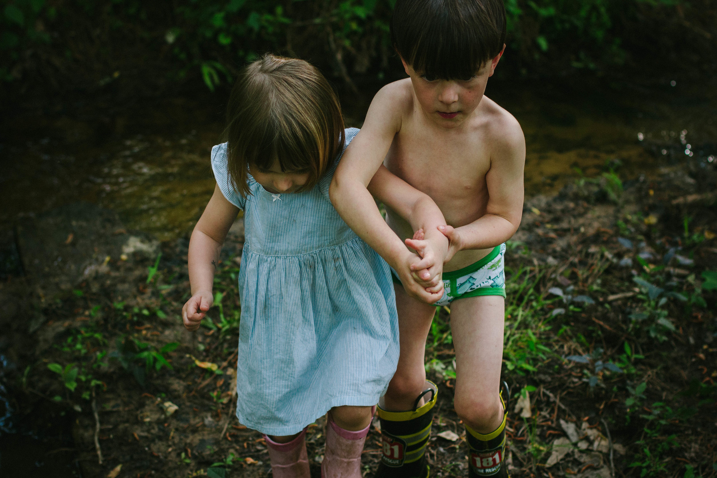 A small boy helping a small girl by holding her arm to cross a creek