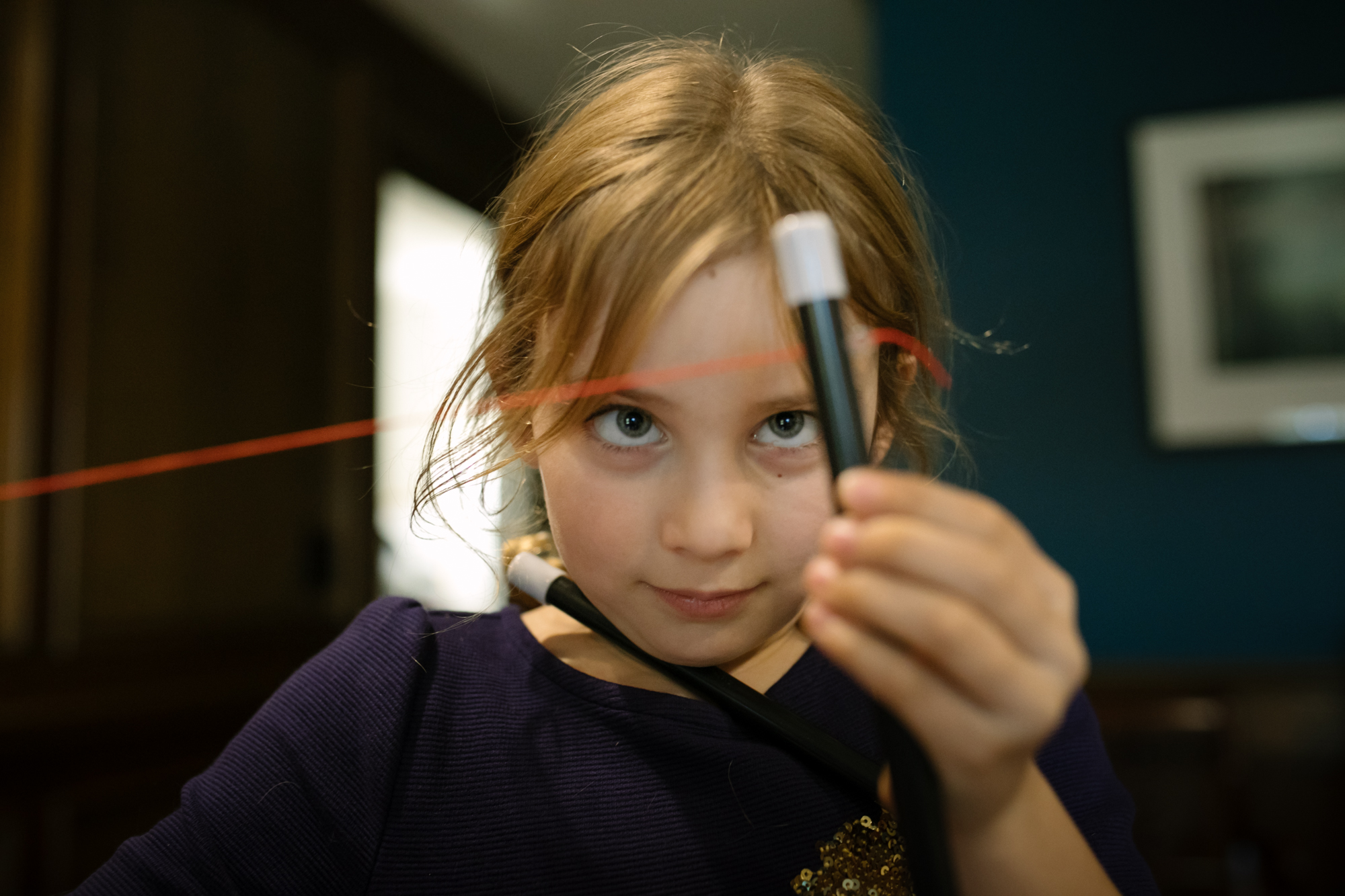 A girl looks at a string attached to a magic wand.