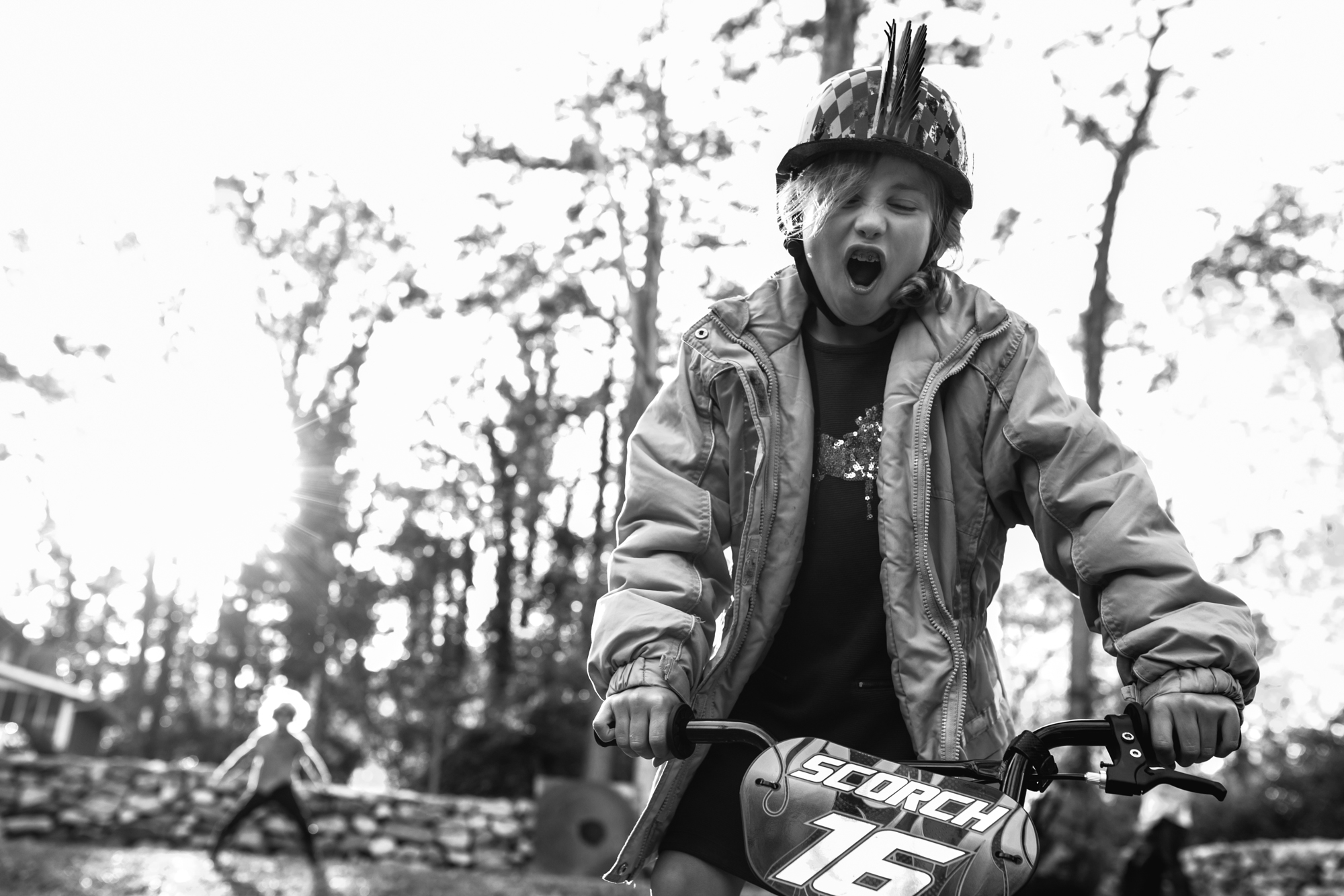 A girl rides a bike with a fierce expression
