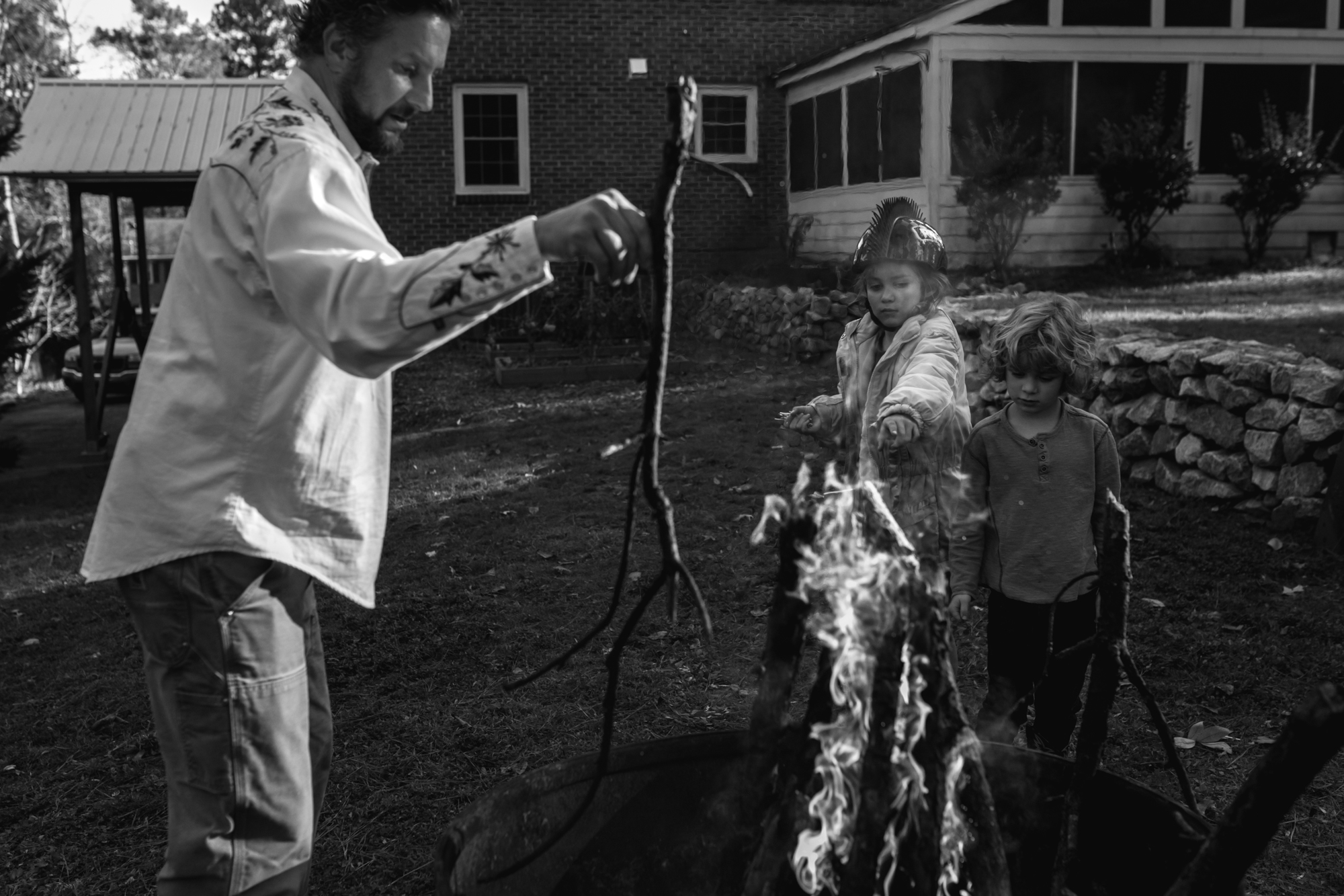 A man and two children throw sticks into a fire