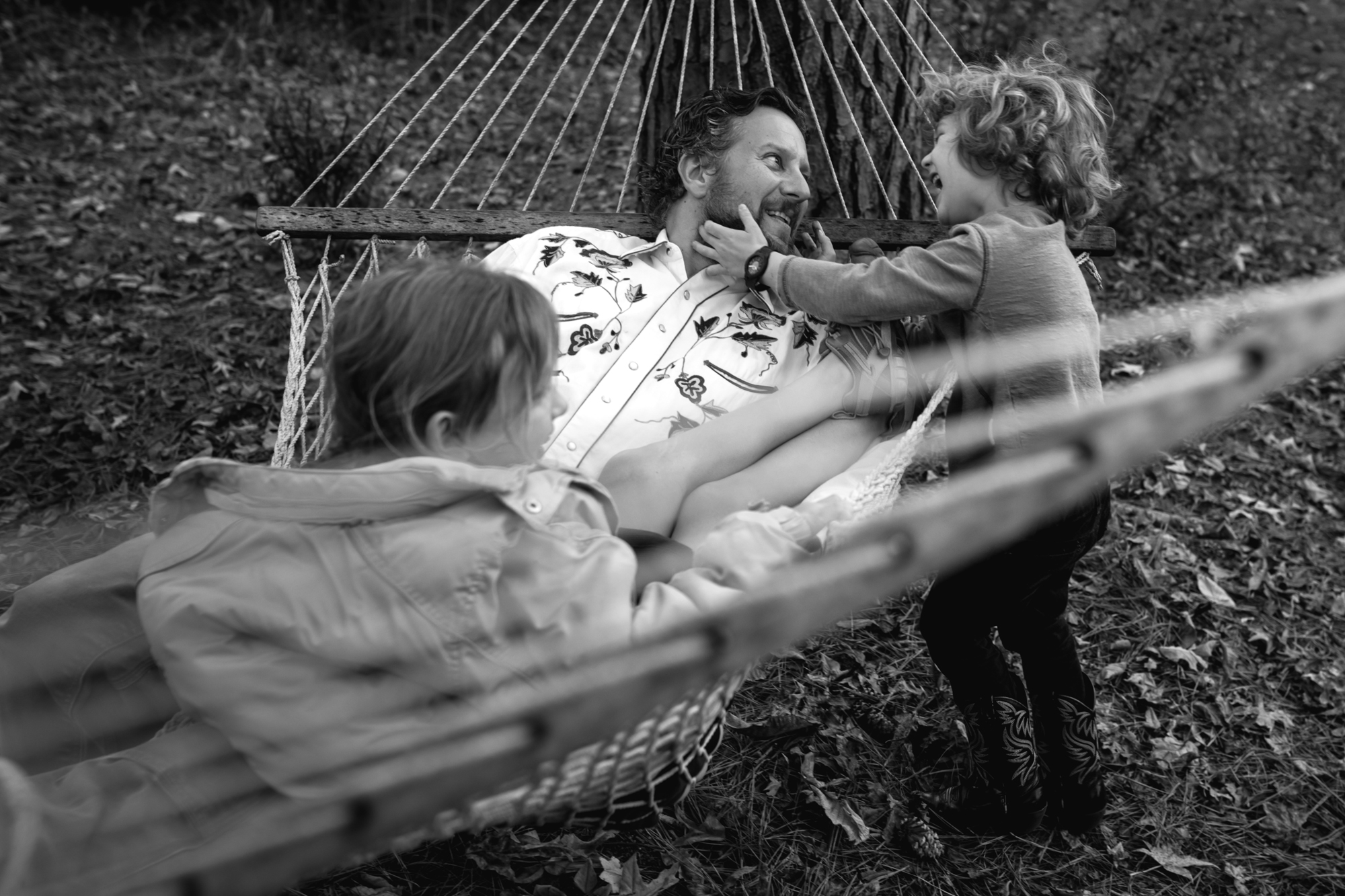 A boy holds his dad's face who is on a hammock with a girl