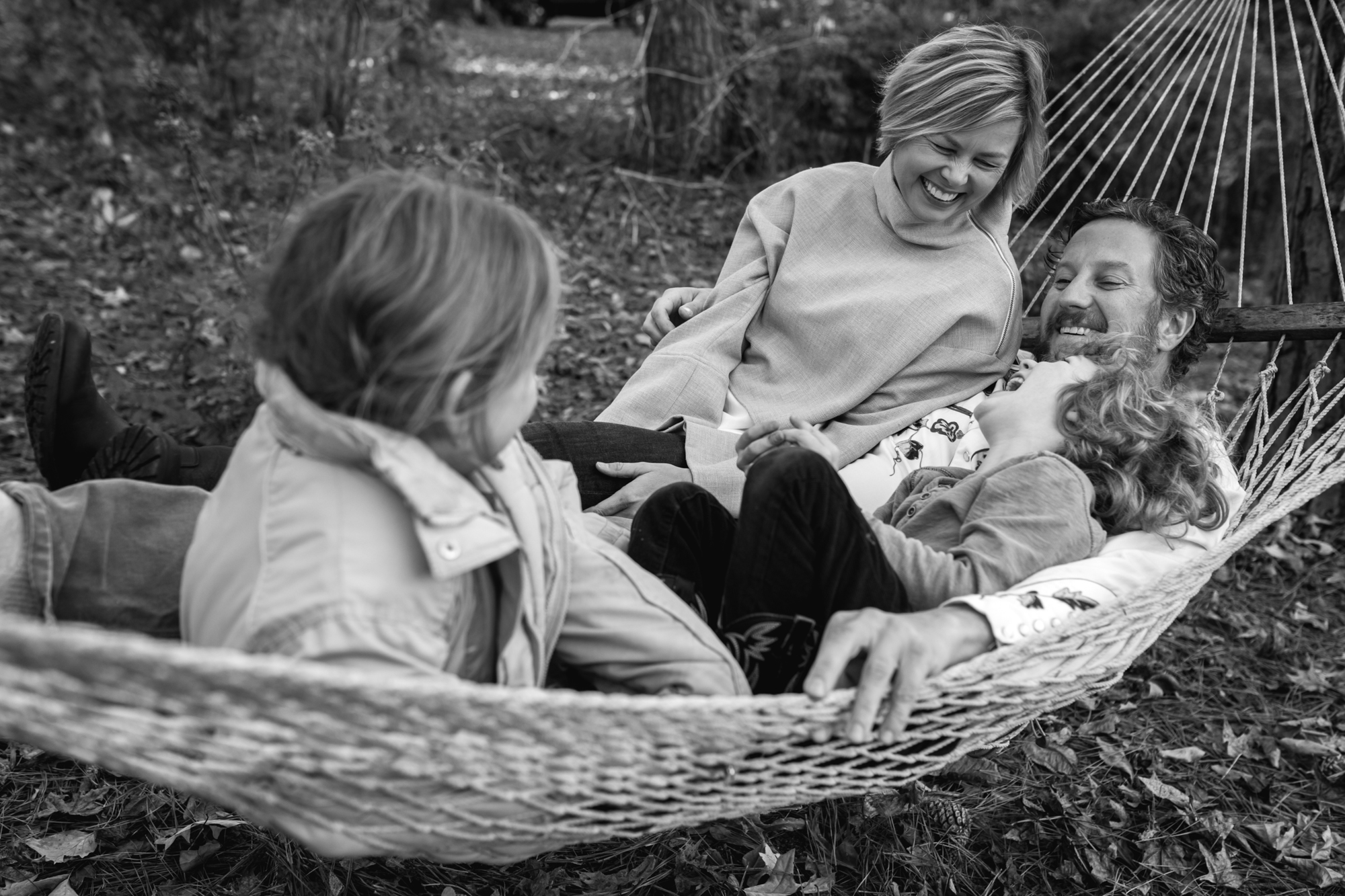 A family laughs and lies on a hammock
