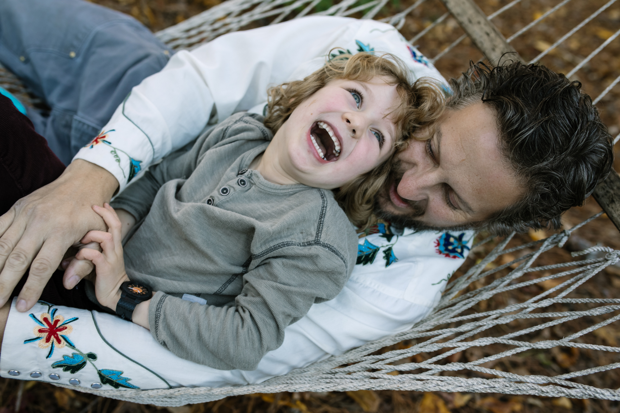 A boy and his dad lie on a hammock laughing