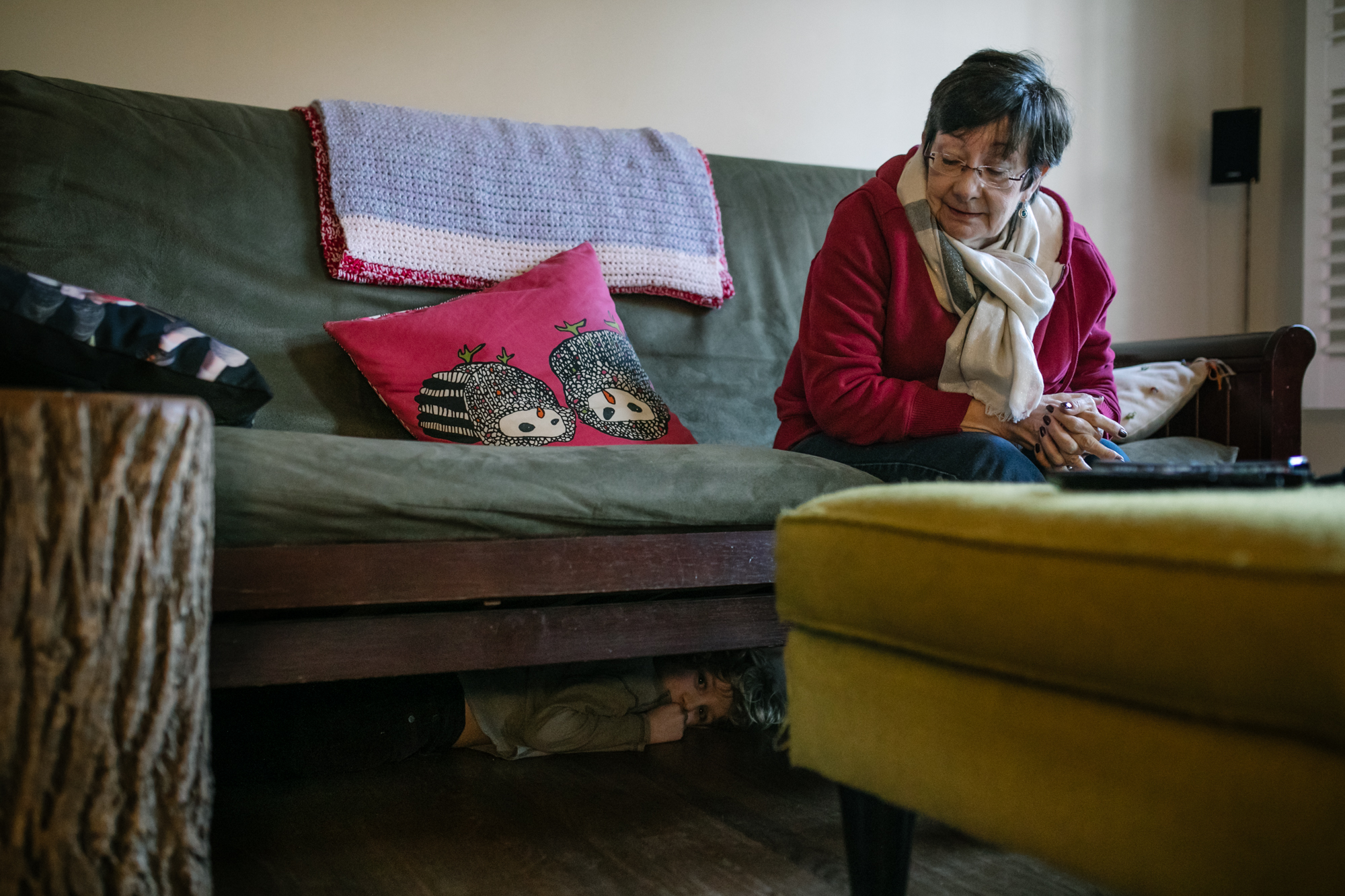 An older woman sits on a couch as a boy hides underneath