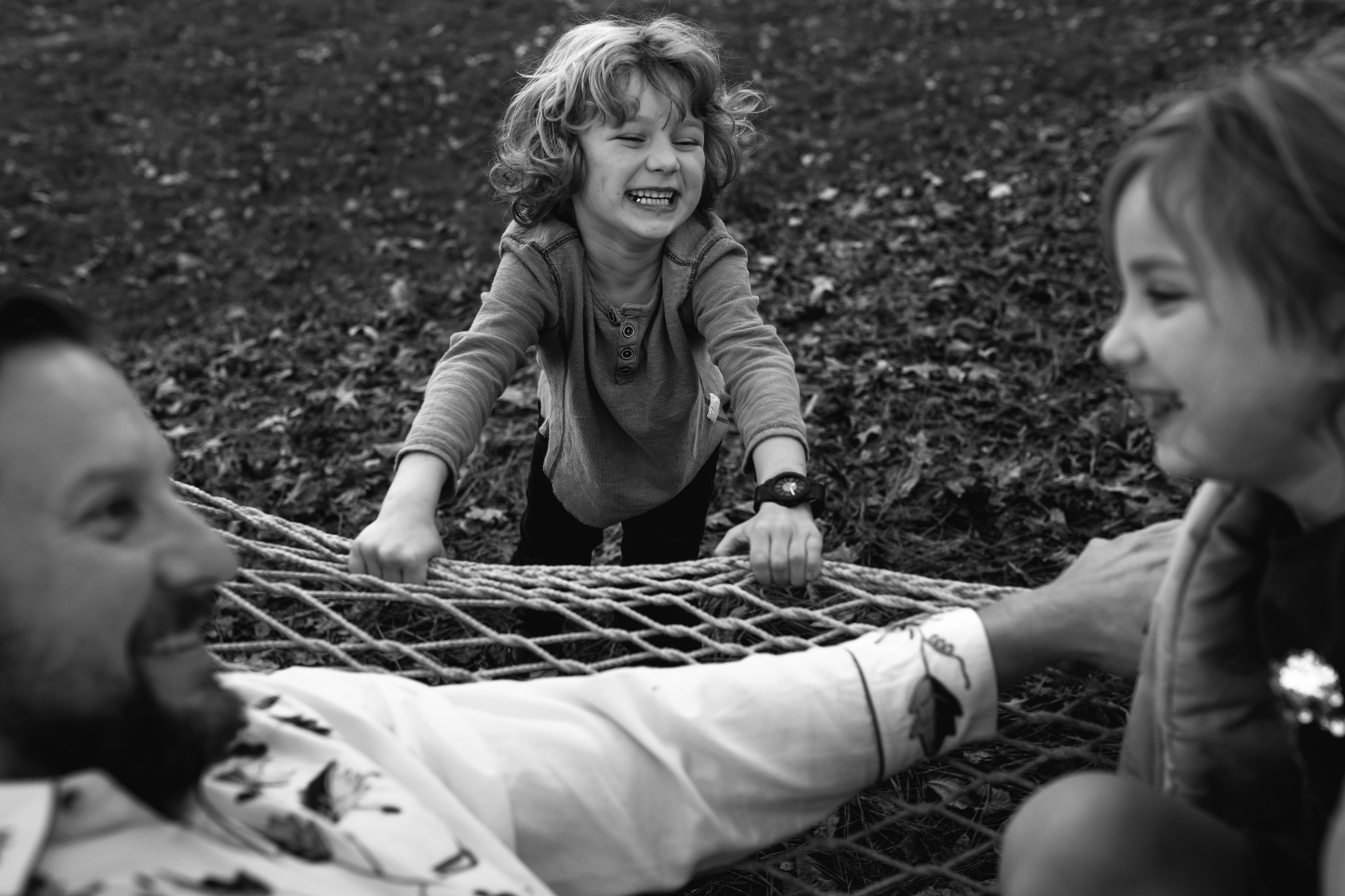 Boy smiles and pushes dad and sister on a hammock