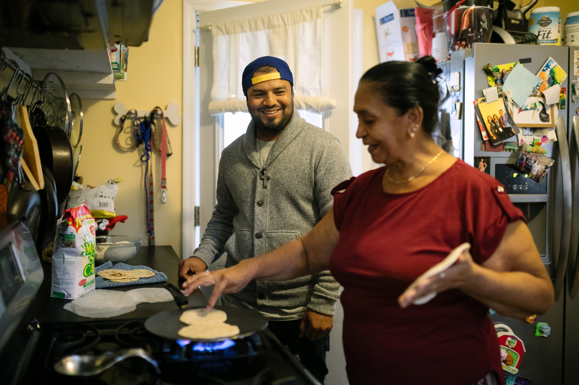 A man looks at his mother as she makes tortillas on the stove