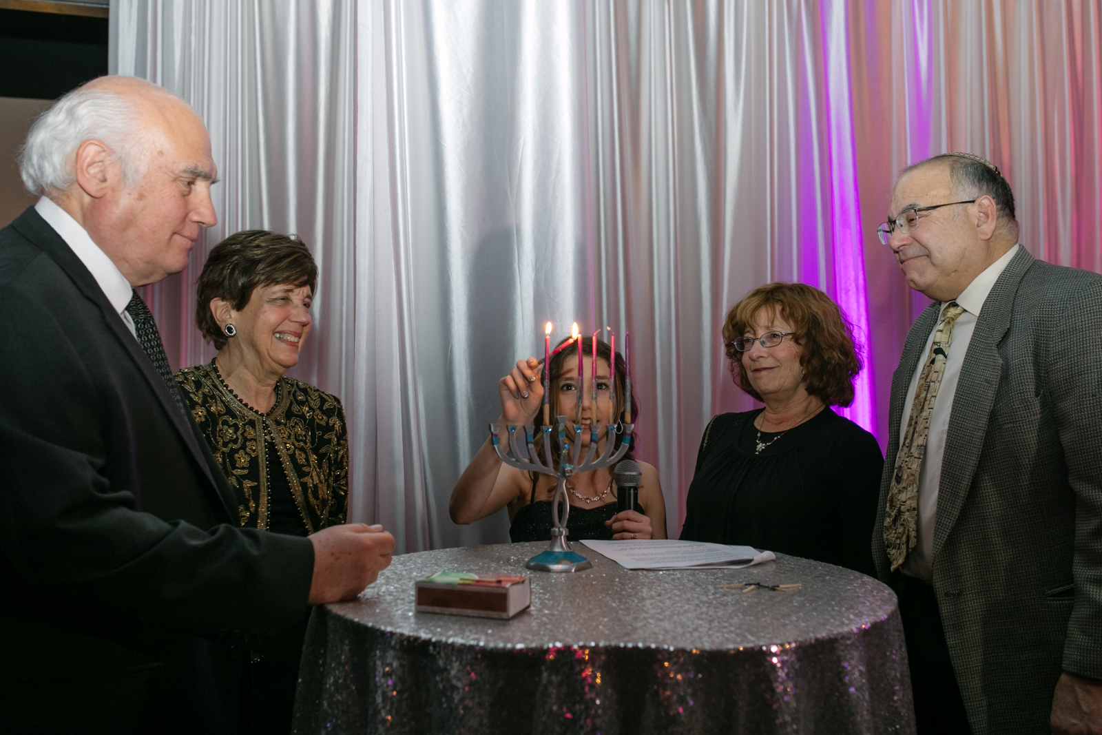 A girl lights the menorah during her bat mitzvah with her grandparents beside her