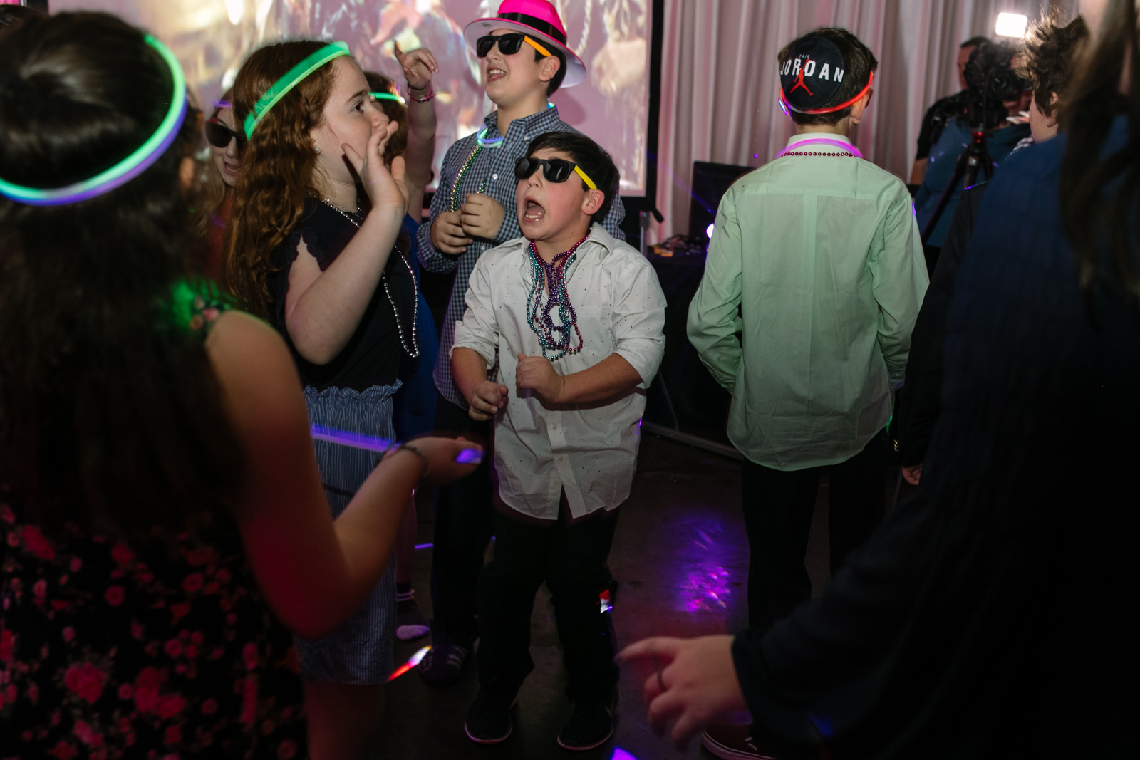 A boy wearing sunglasses and beads dances with others during a bat mitzvah