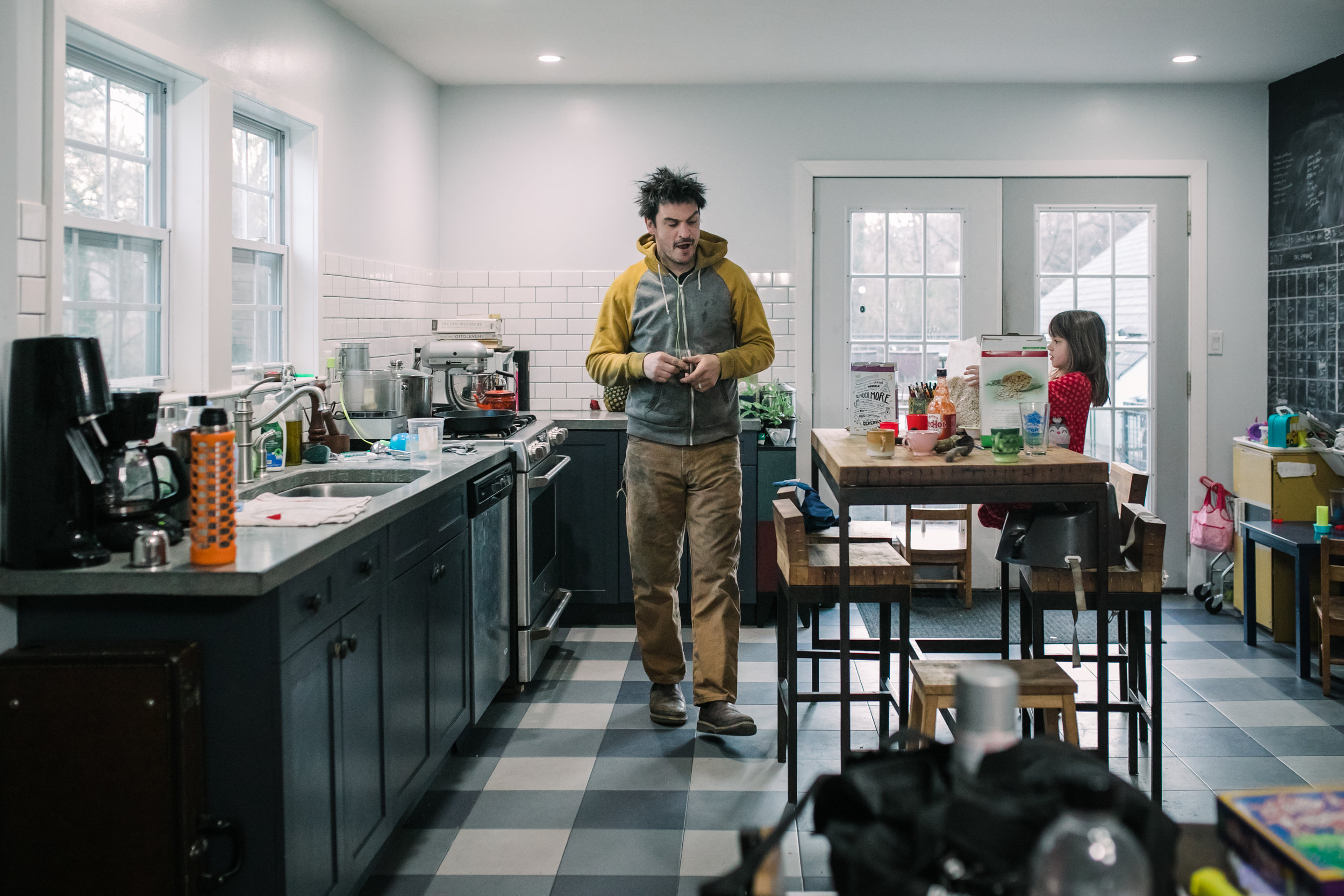 Man yawns in a kitchen and a girl eats breakfast