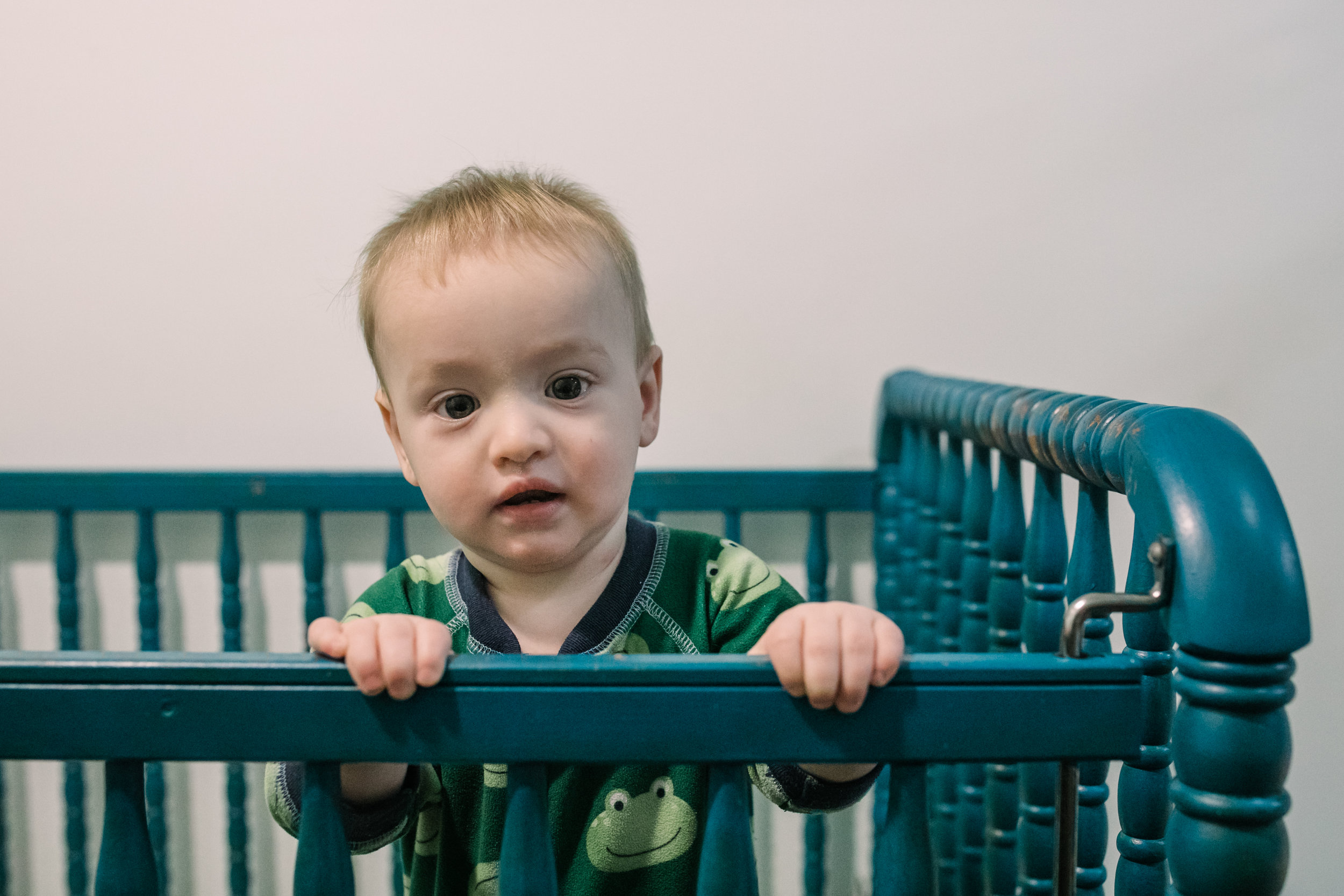 Baby boy stands up in crib and looks in the camera