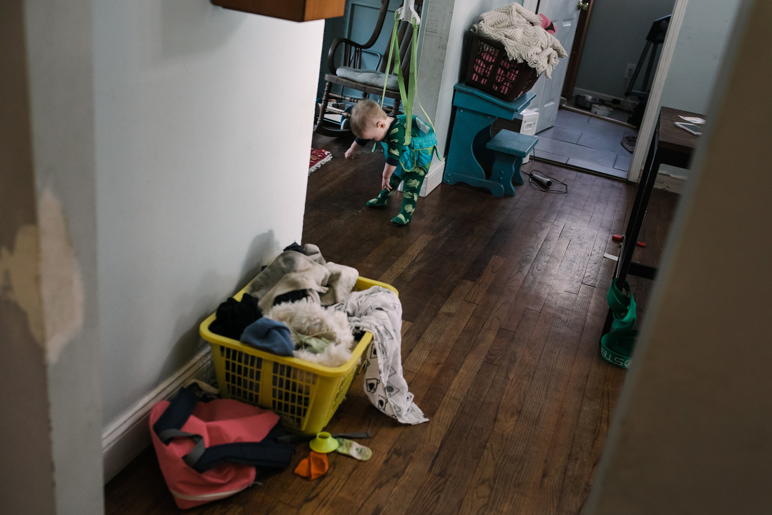 baby slumps over in a jumper flanked by full laundry baskets