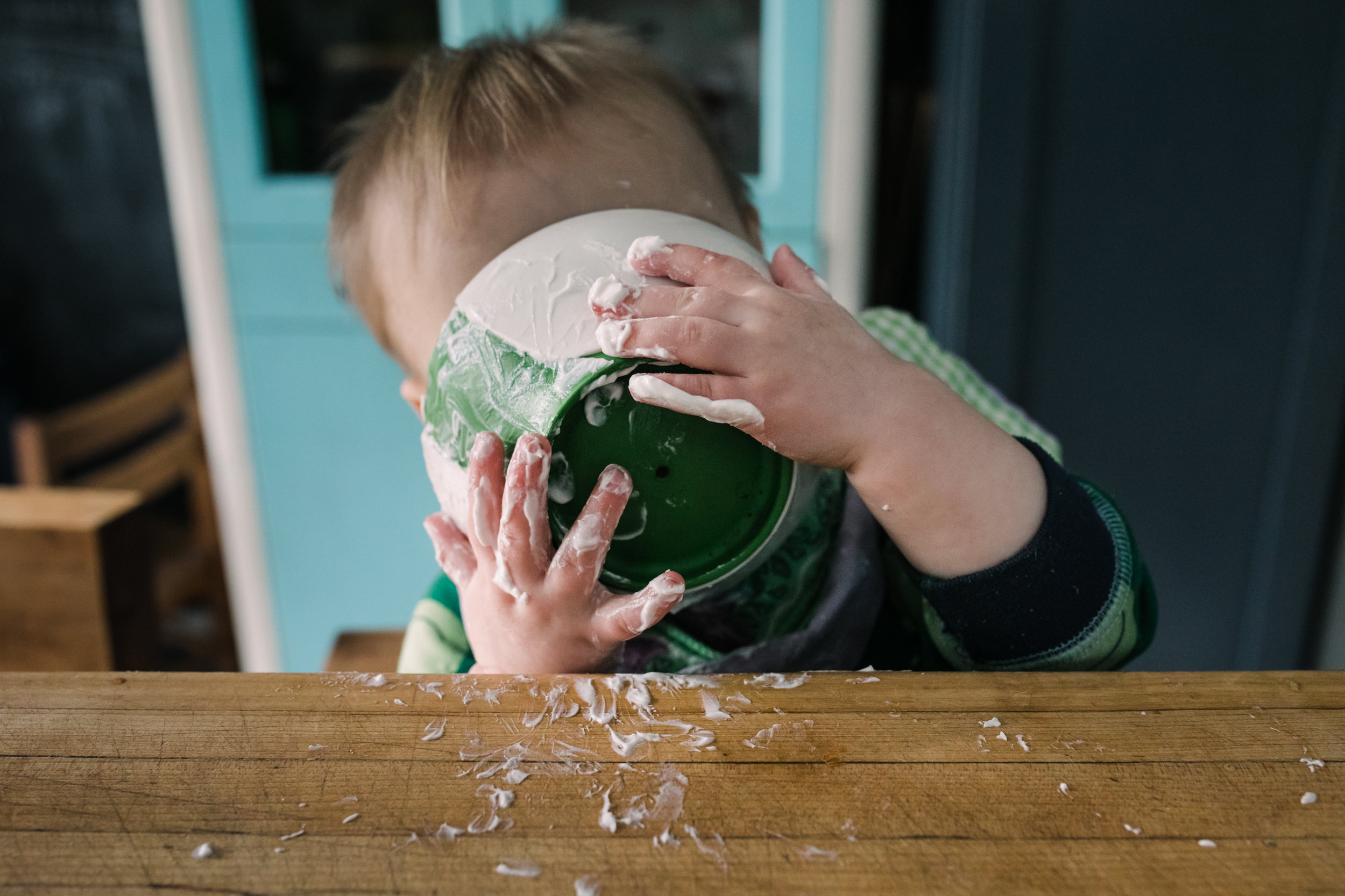 Baby holds bowl of yogurt close to his face
