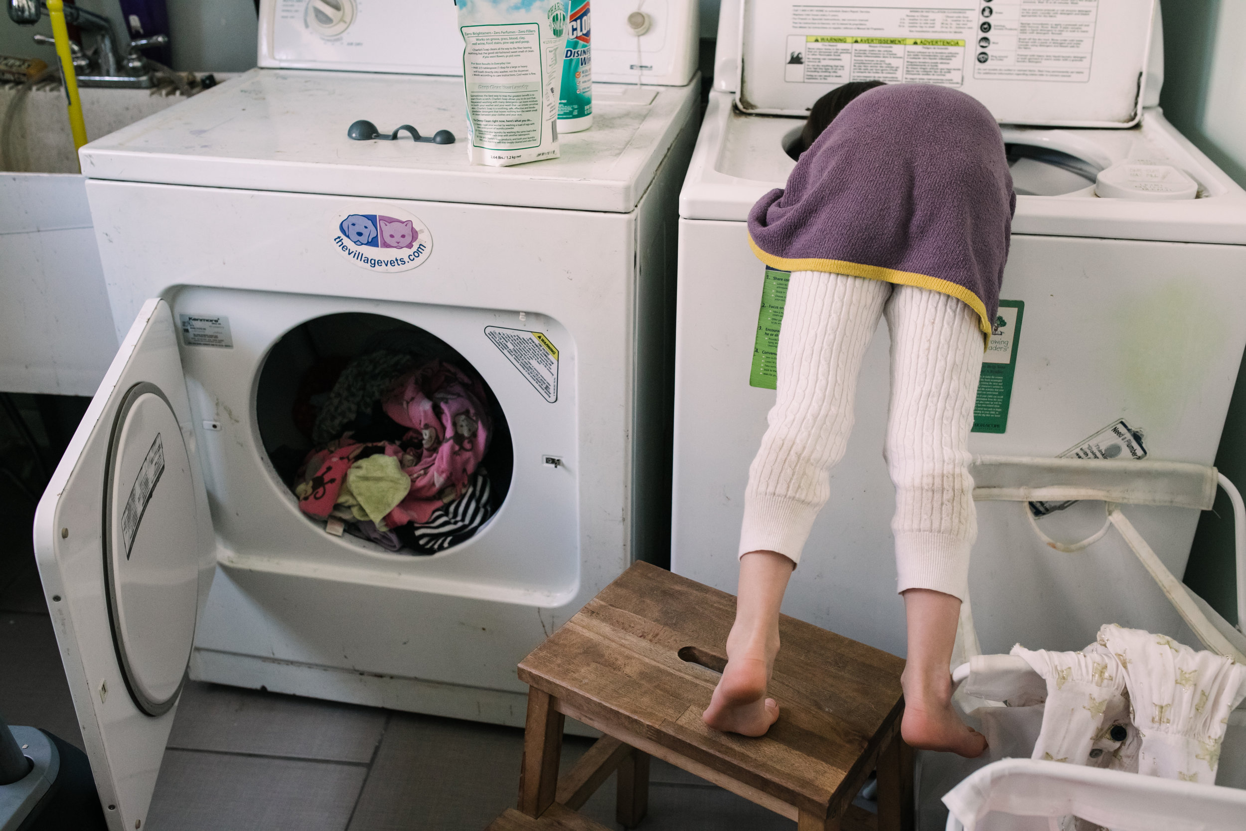 Child stands on a stool and leans over into the washing machine