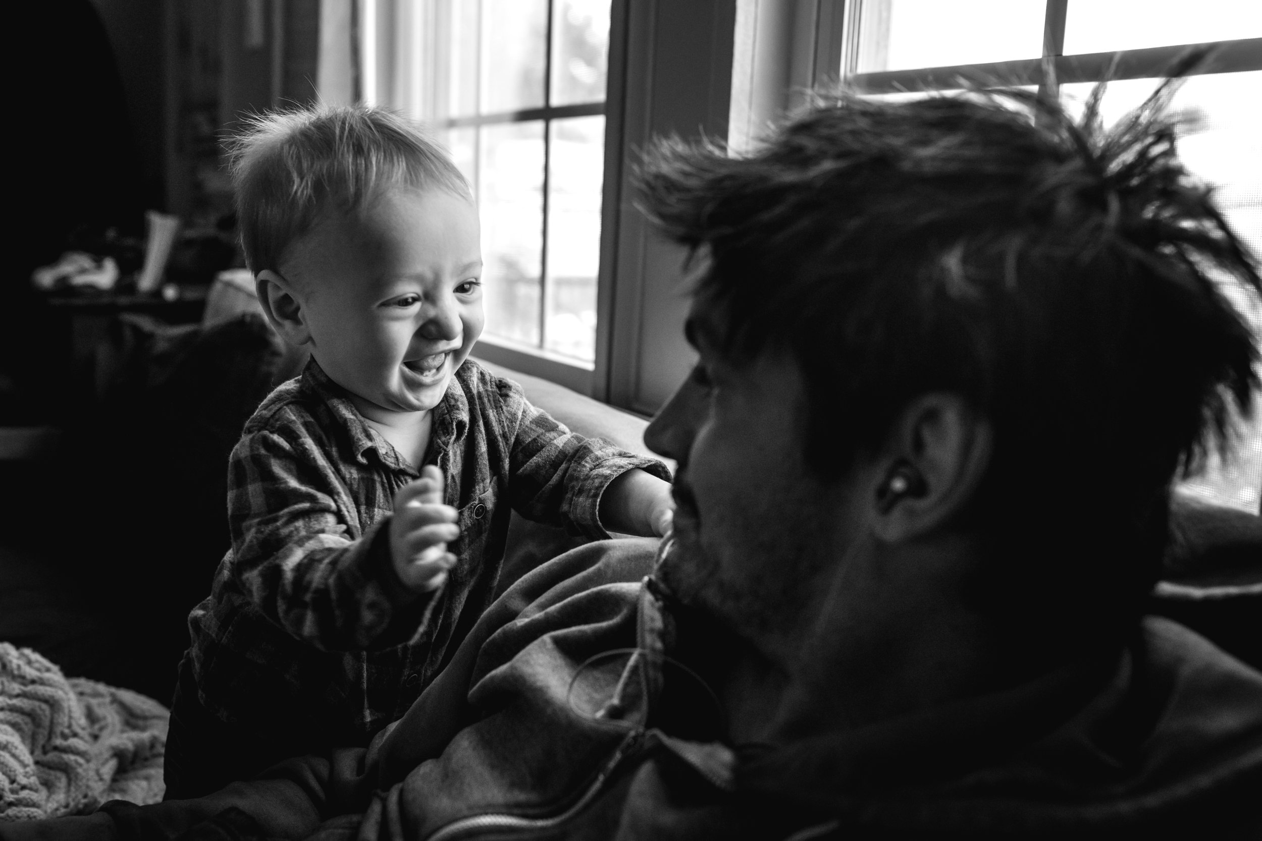 baby smiles and looks at his dad