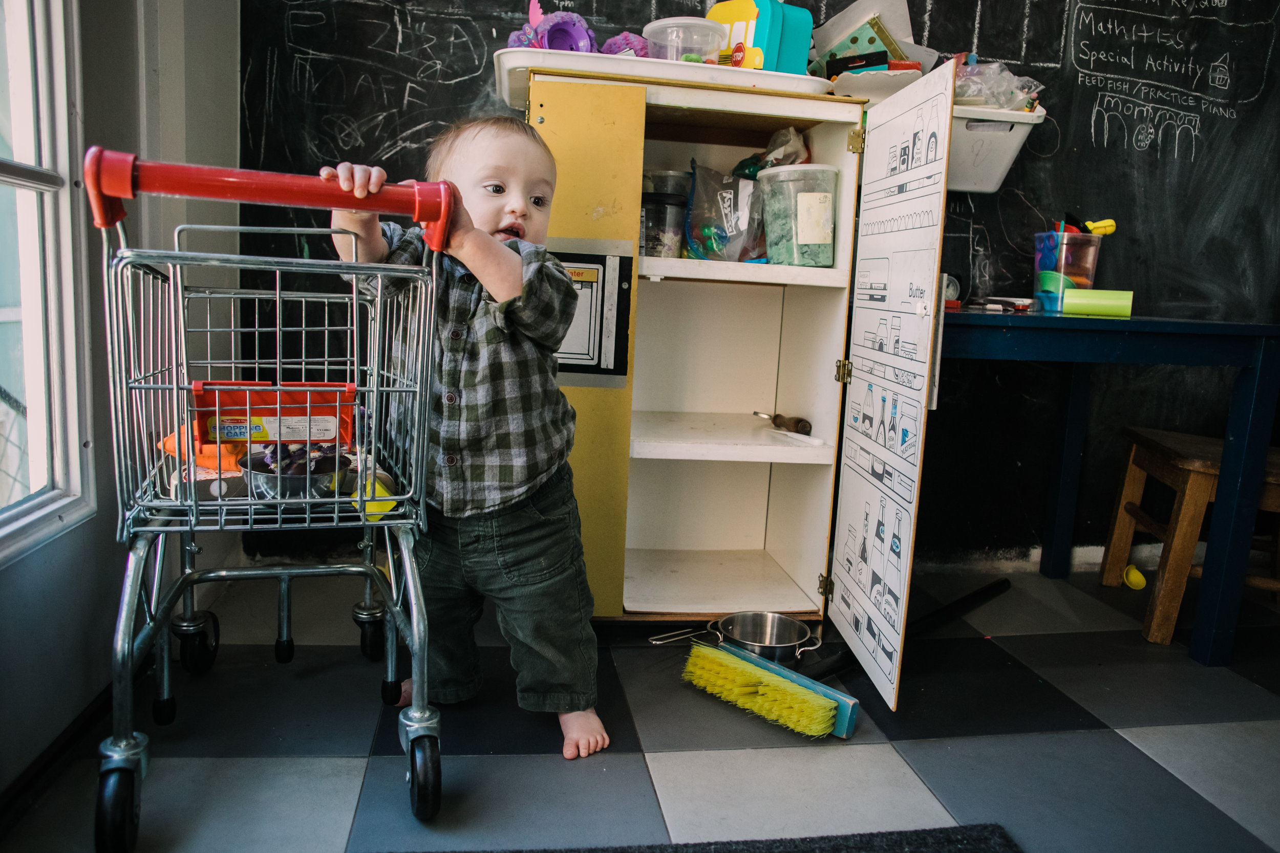 baby holds  on to child's shopping cart with a pretend kitchen