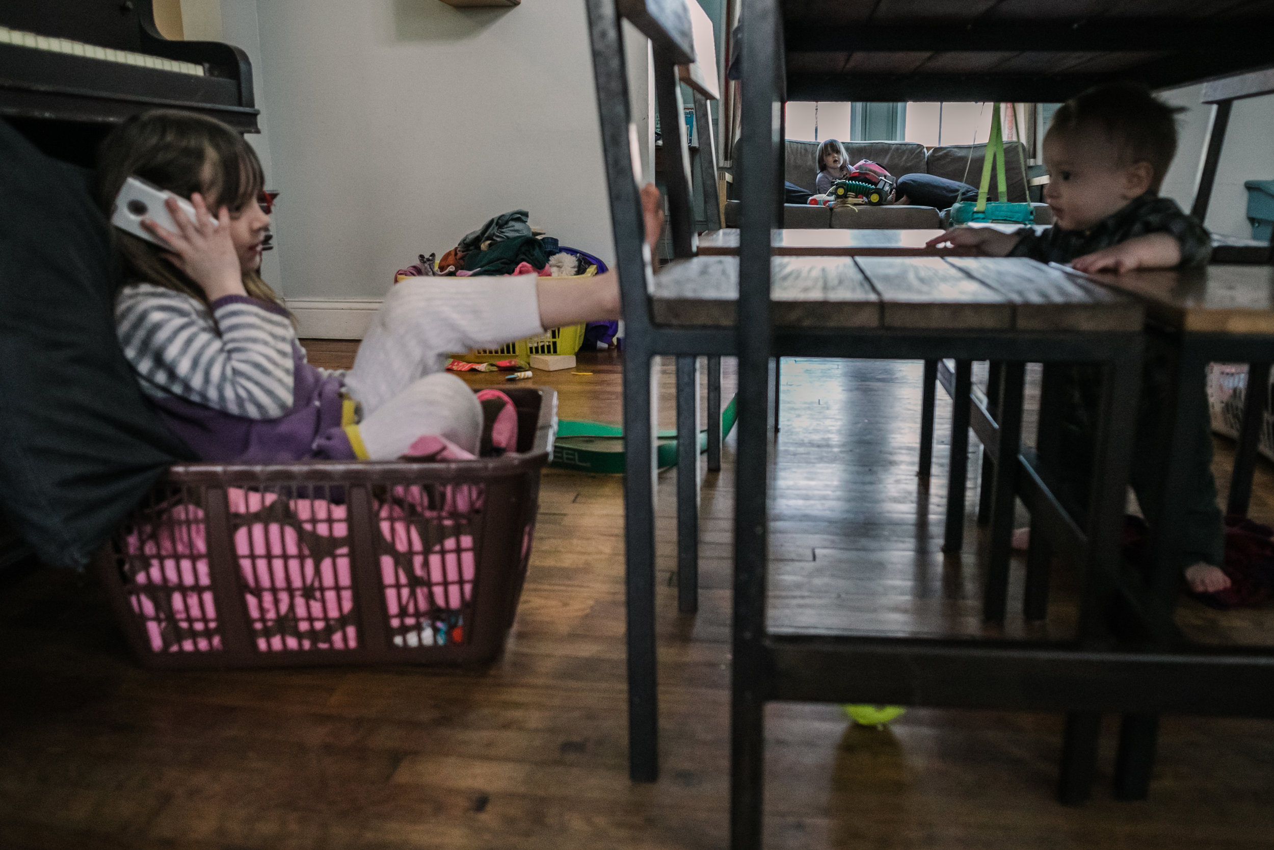 A child sits on a couch as a baby stands under a table and a girl sits in a laundry basket and talks on a phone