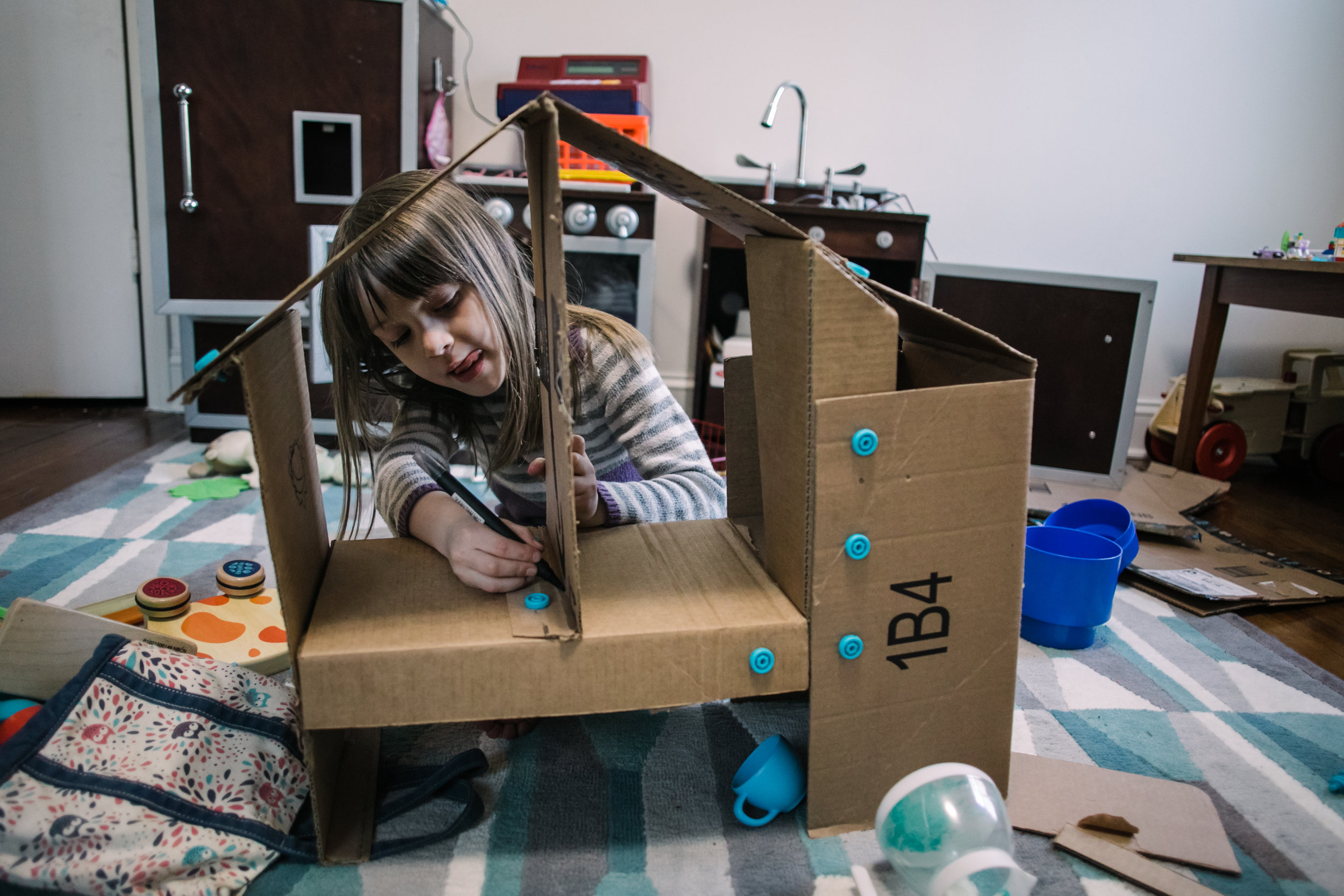 Girl writes on cardboard house with marker while sticking her tongue out