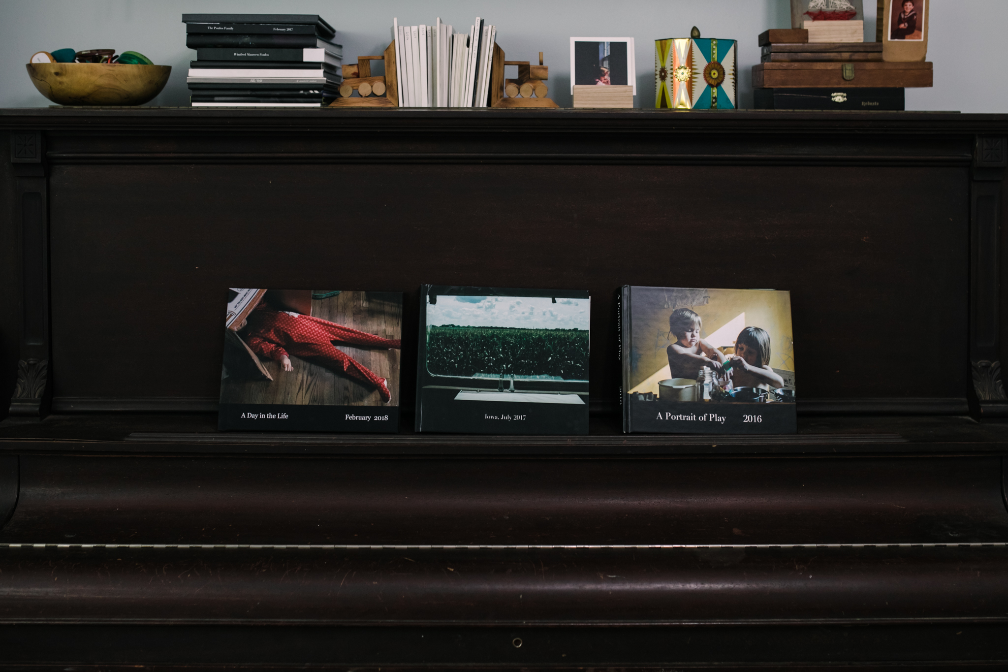 three photo albums on a piano