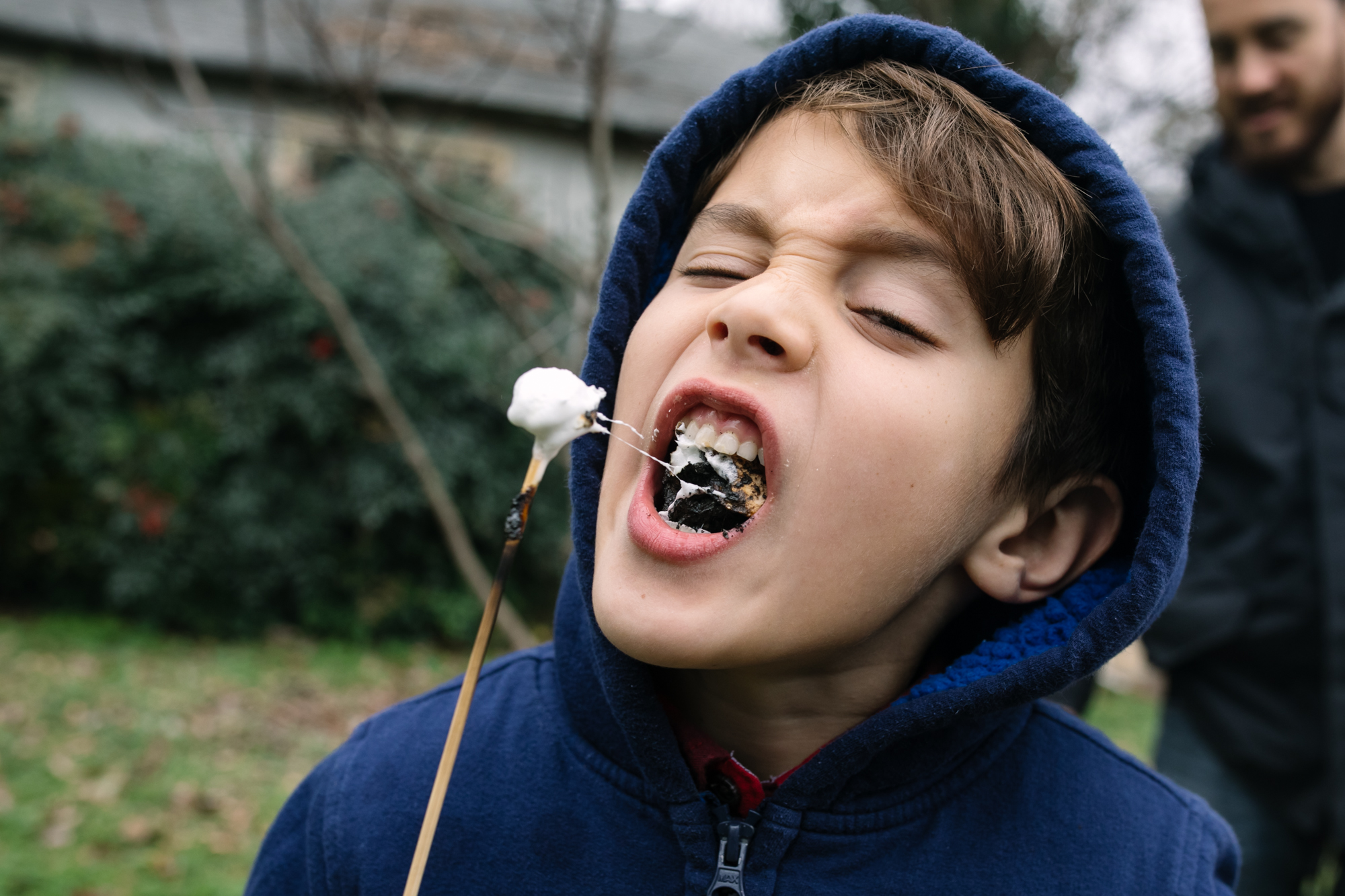 a boy bites a roasted marshmallow off of a stick