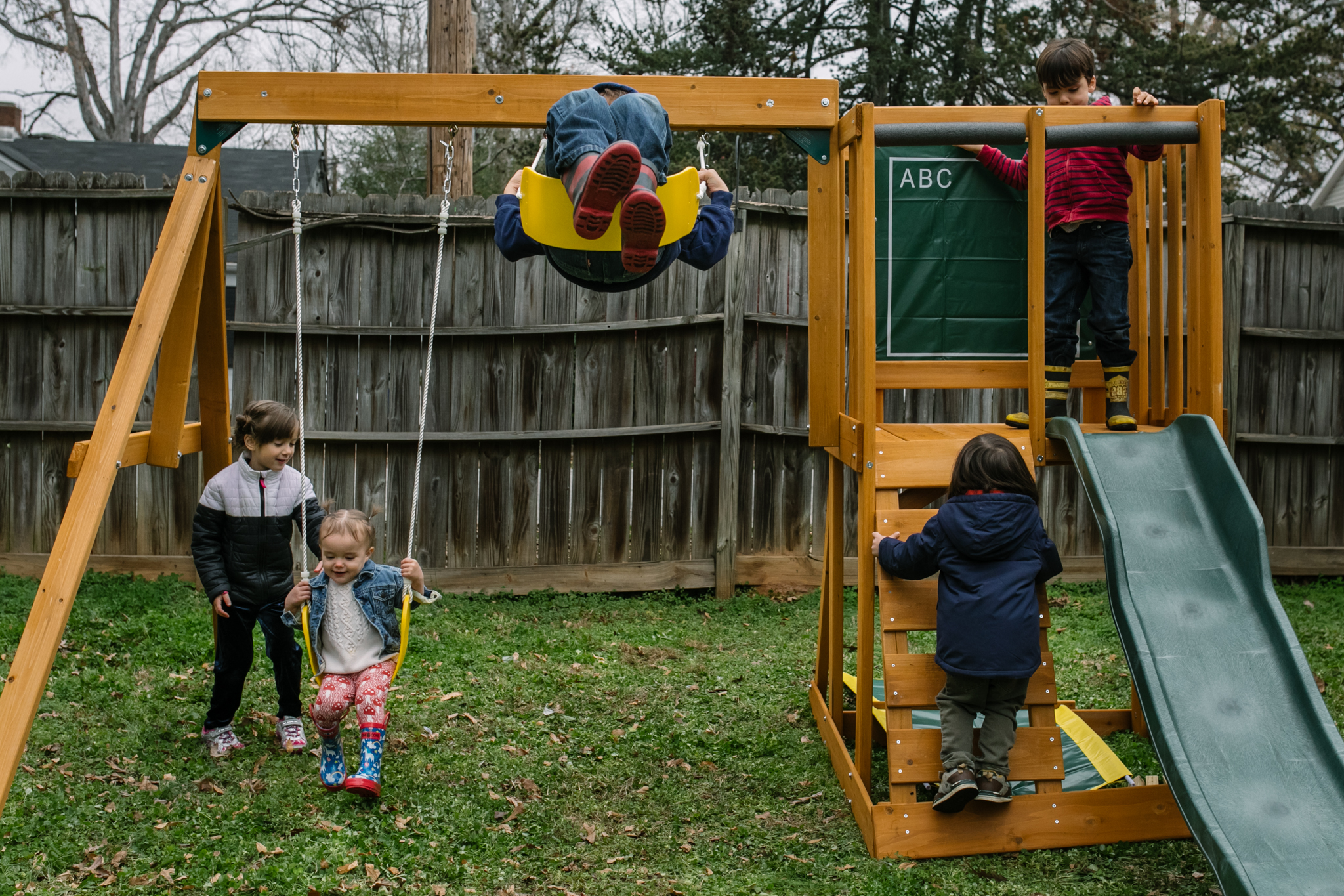 Cousins play together on a new swingset